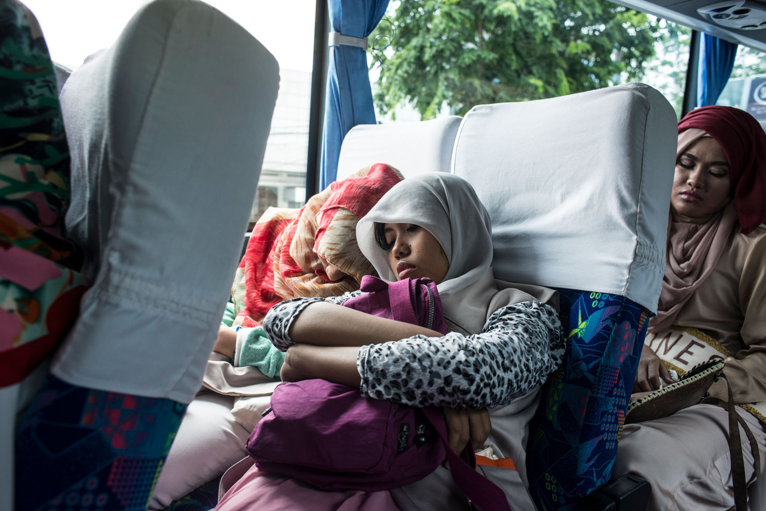Two LO's or Logistic officers, who are each assigned to a girl as a defacto babysitter, sleep on the bus between events.