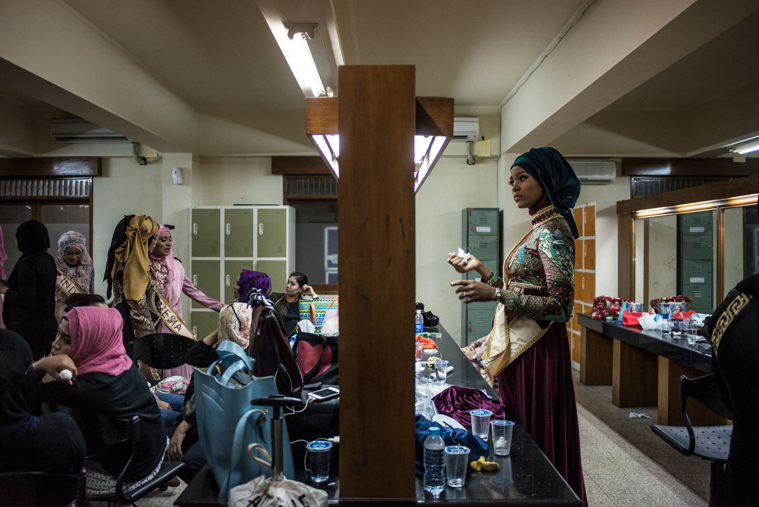 After advancing to the second round, Miss Nigeria, Bilqis Adebayo, drinks water while stylists work on her hijab. The Grand Finale of the Miss Muslimah World Competition on November 21st, 2014 in Yogakarta, Indonesia.