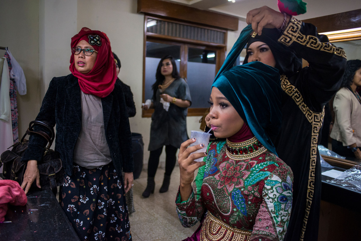 After advancing to the second round, Miss Nigeria, Bilqis Adebayo drinks water while stylists work on her hijab. The Grand Finale of the Miss Muslimah World Competition on November 21st, 2014 in Yogakarta, Indonesia.