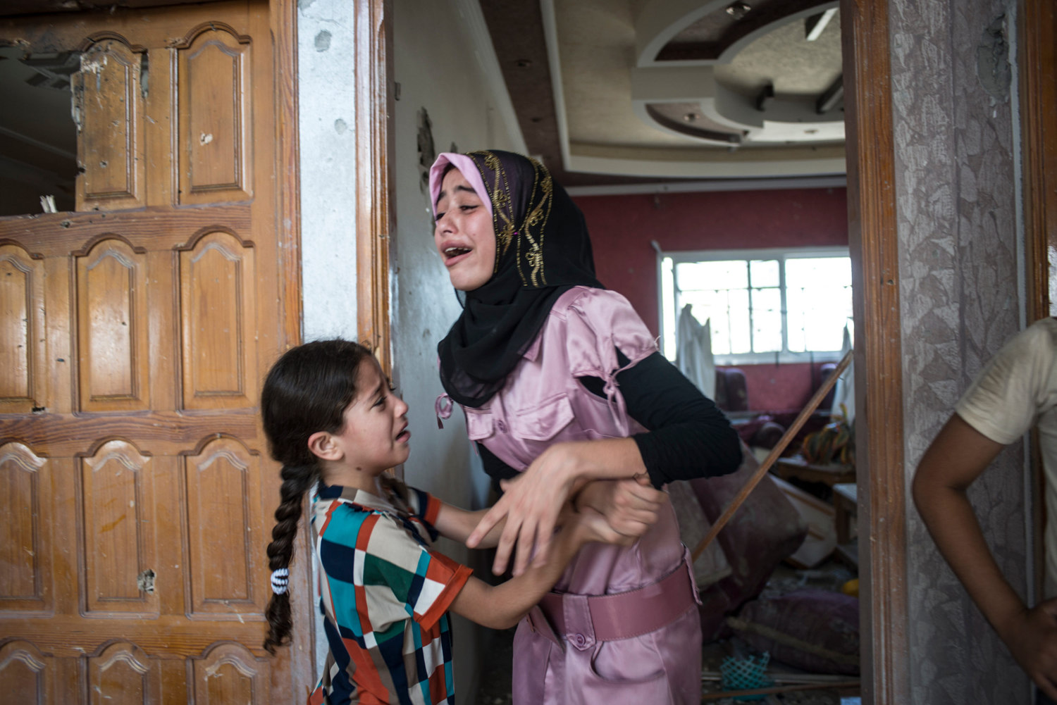 Haneen Harara, 15, and her sister Yasmeen Harara 6 cry upon seeing their family home for the first time. The sisters have lived in this house their whole life and have no where else to go. They are currently living in a UN shelter.