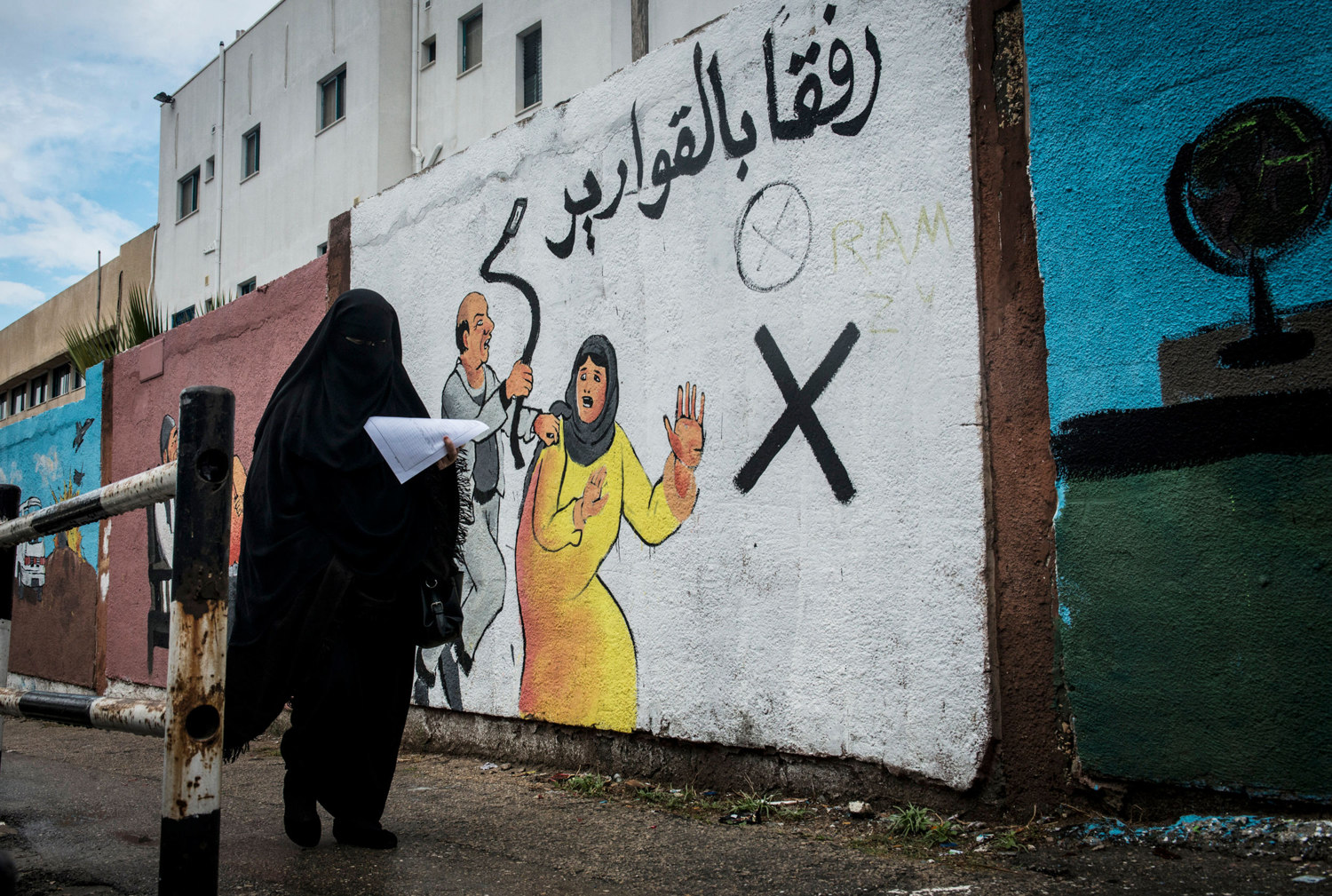 A woman walks by an mural discouraging domestic violence outside if Al-Shifa hospital. According to a 2012 study, some 37% of women are subjected to domestic violence by their husbands.