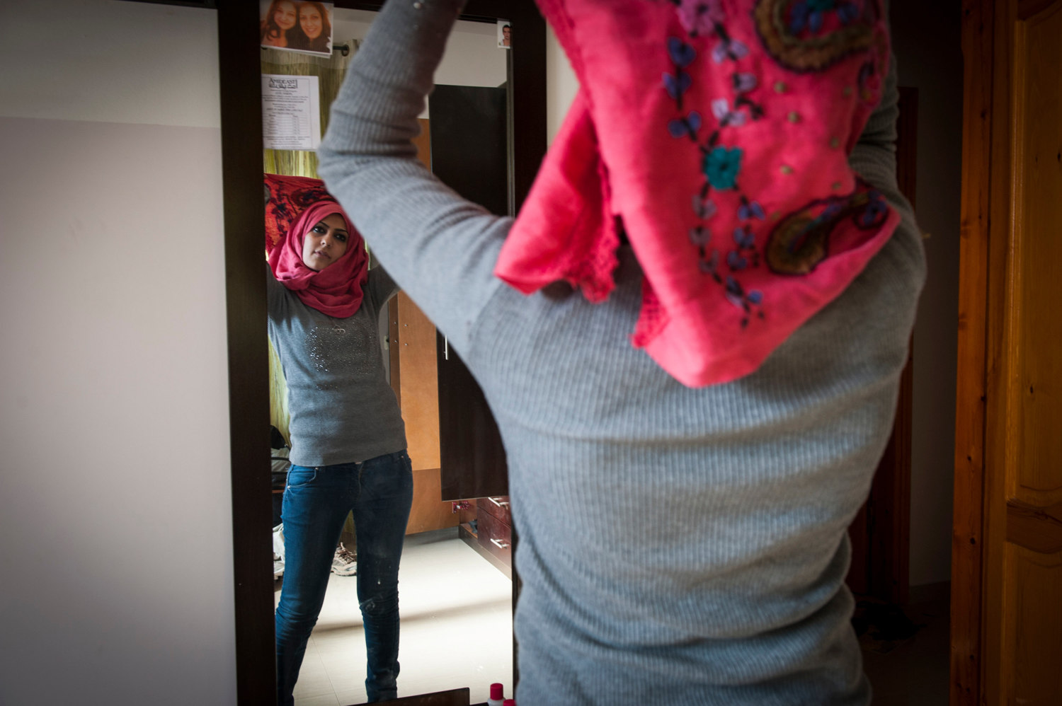 Few girls in Gaza are uncovered, here Doaa carefully does her hijab before leaving the house.