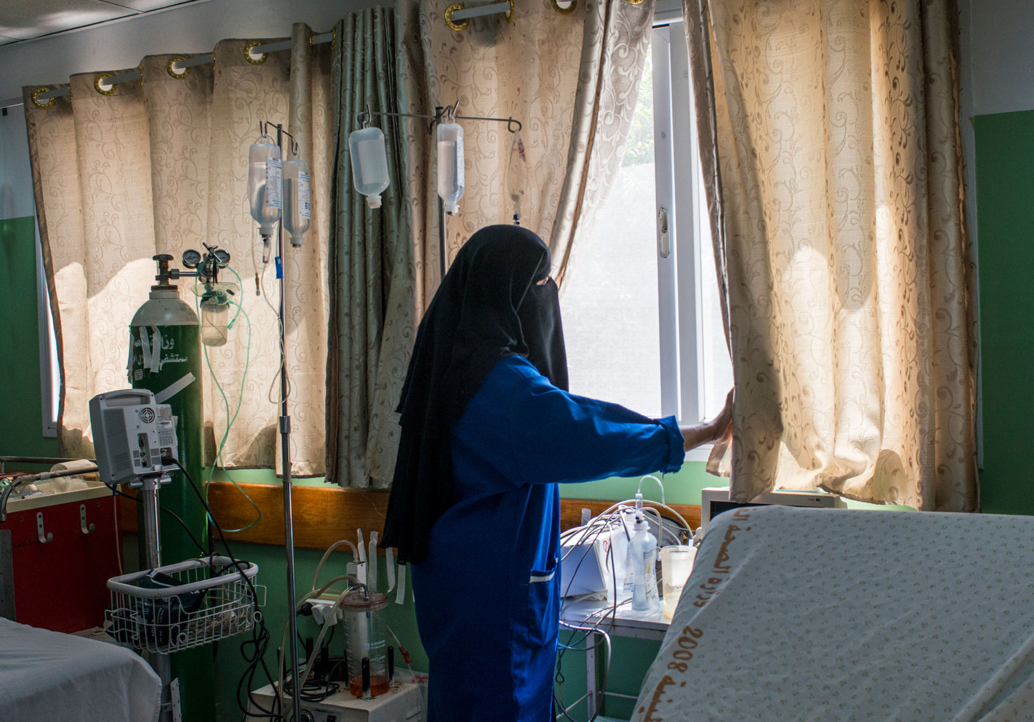 A nurse looks out the window of a hospital in Rafah waiting for more ambulances to bring in corpses after the ground invasion in Gaza.