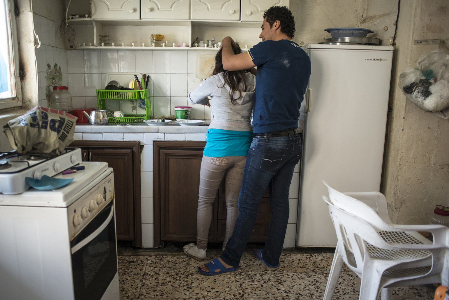 Another couple wash dishes and play around at their shared home with the Mirza family in the Cultural Center on October 30th, 2014 in Midyat, Turkey.
