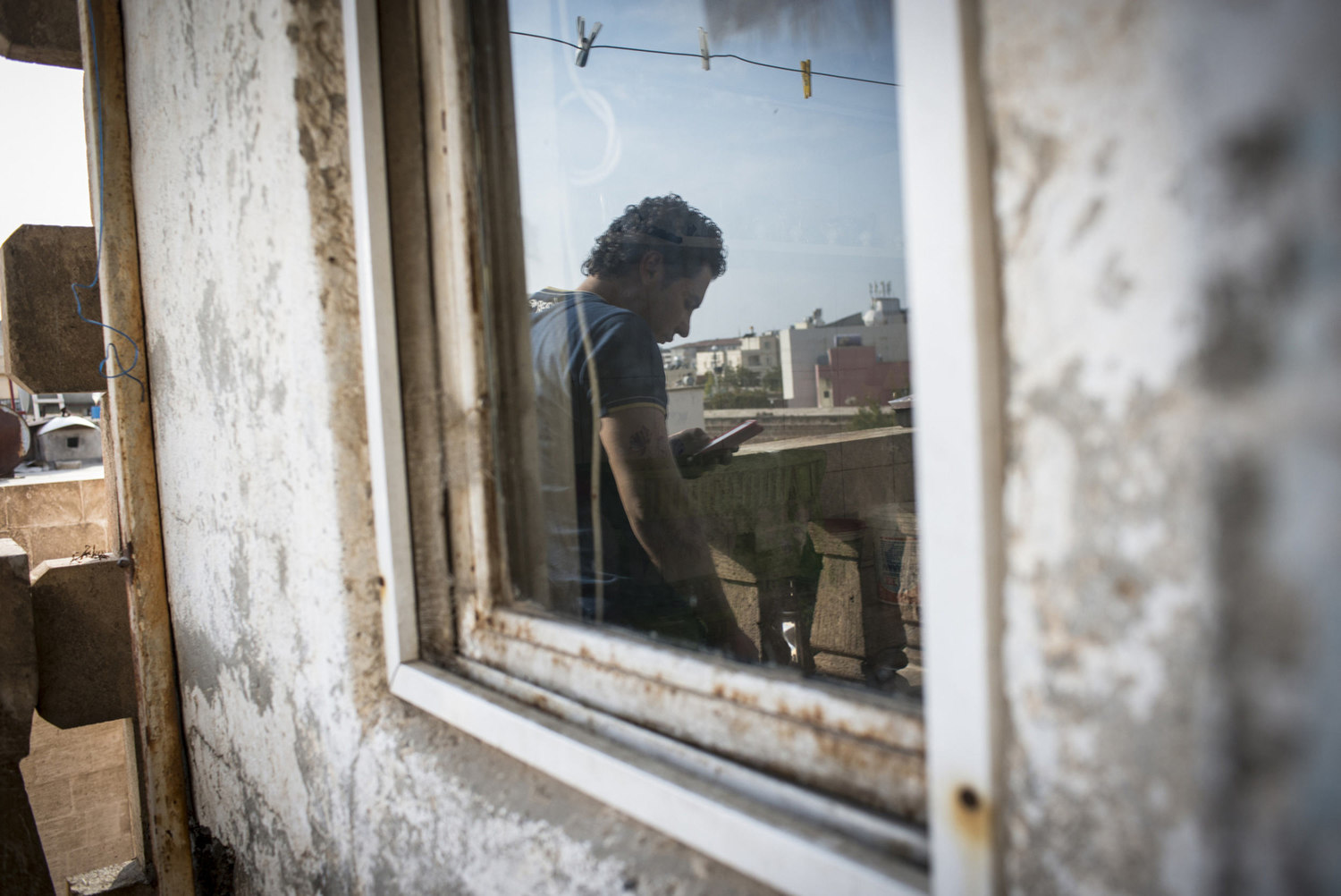 A Syrian refugee makes a call to Syria outside of his temporary home in the Cultural Center on October 30th, 2014 in Midyat, Turkey.