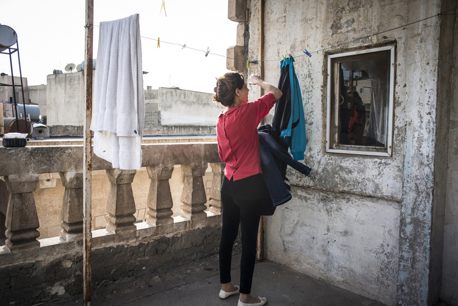 Ninwa Mirza takes in the laundry from outside of her temporary home in the Cultural Center on October 30th, 2014 in Midyat, Turkey.