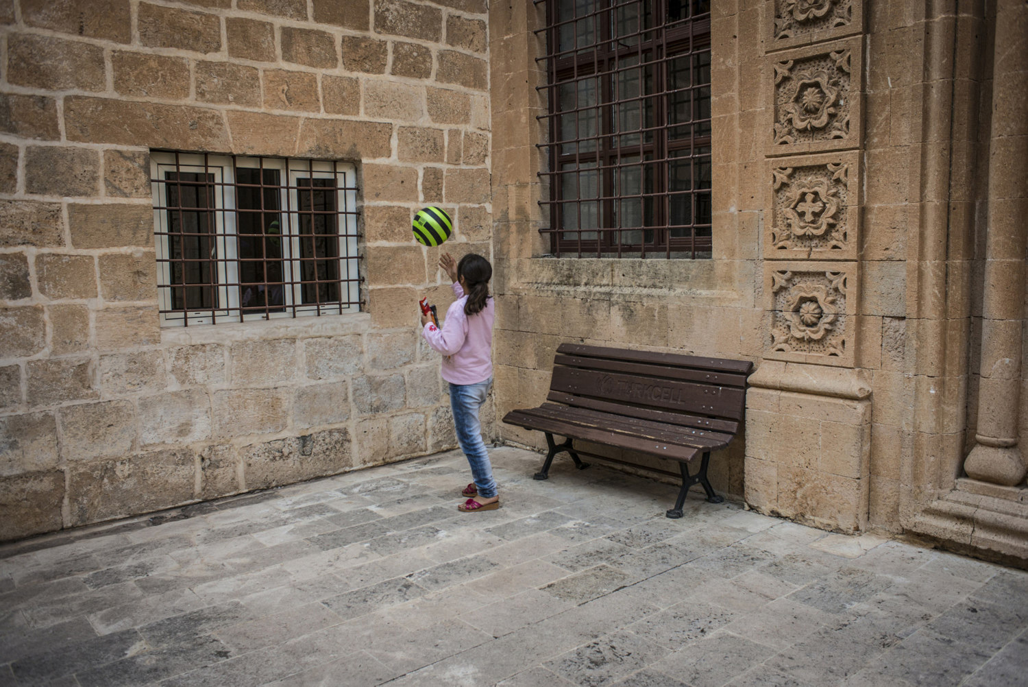 An Assyrian girl plays with a ball on the walls of the church of Mor Barsaumo before her Aramaic lesson on October 30th, 2014.