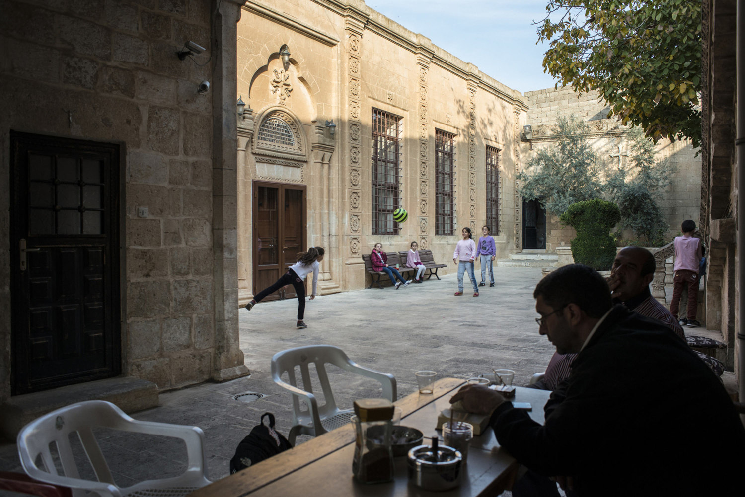 Decon Ayhan Gürkan,(l) reads from a religious book in the courtyard of Mor Barsaumo before teaching an Aramaic lesson on October 30th, 2014.