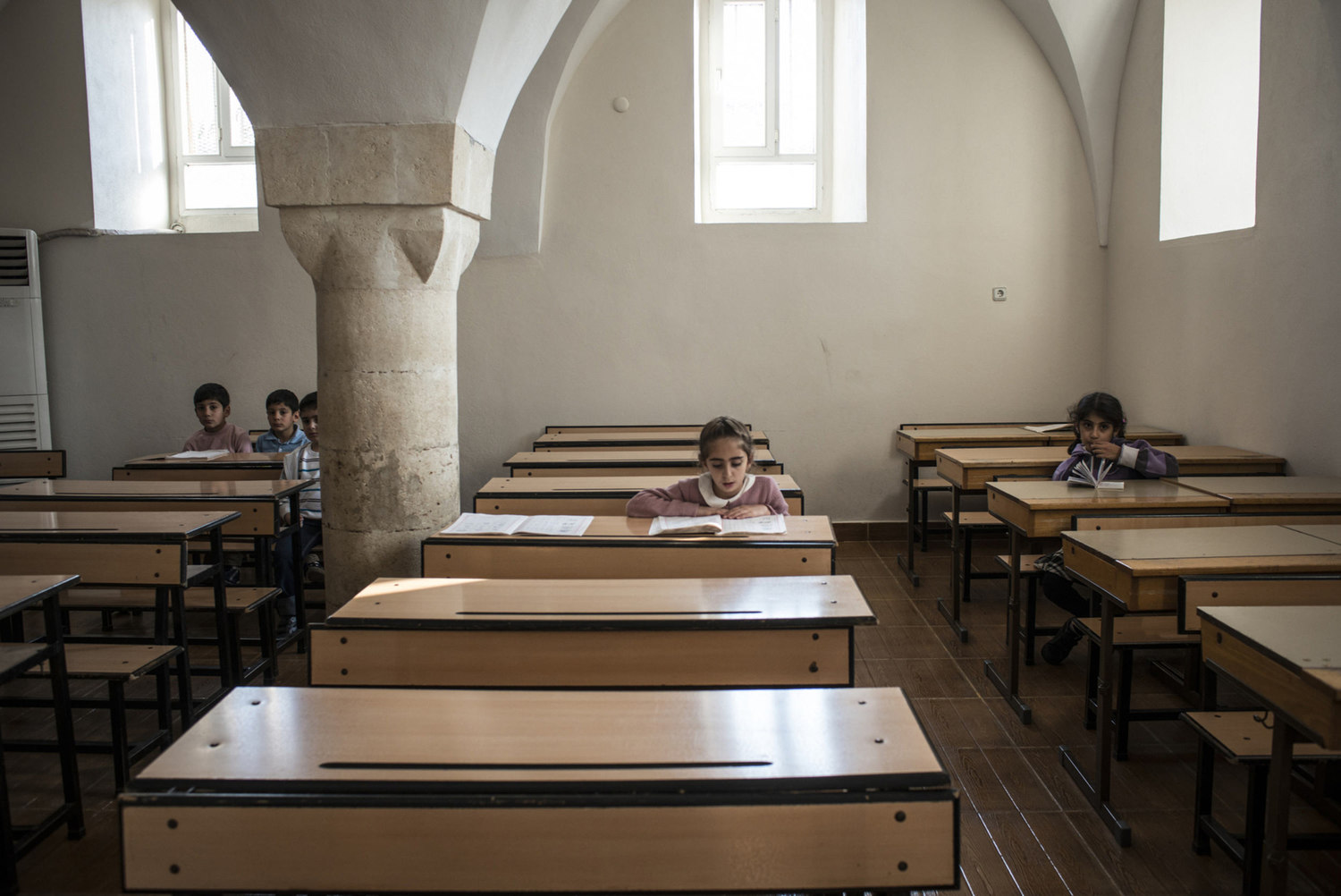 A girl reads during her Assyrian class in the classroom of Mor Barsaumo church on October 30th, 2014.
