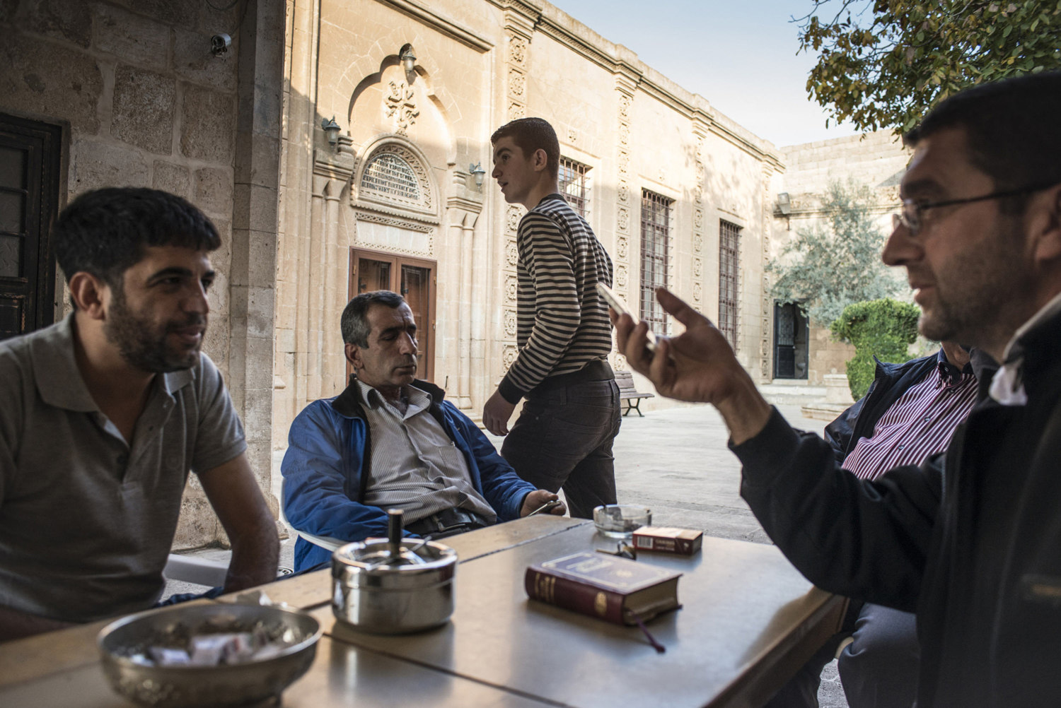 Decon  Ayhan Gürkan,(r) speaks to locals in the cortyard of Mor Barsaumo before teaching an Aramaic lesson on October 30th, 2014.
