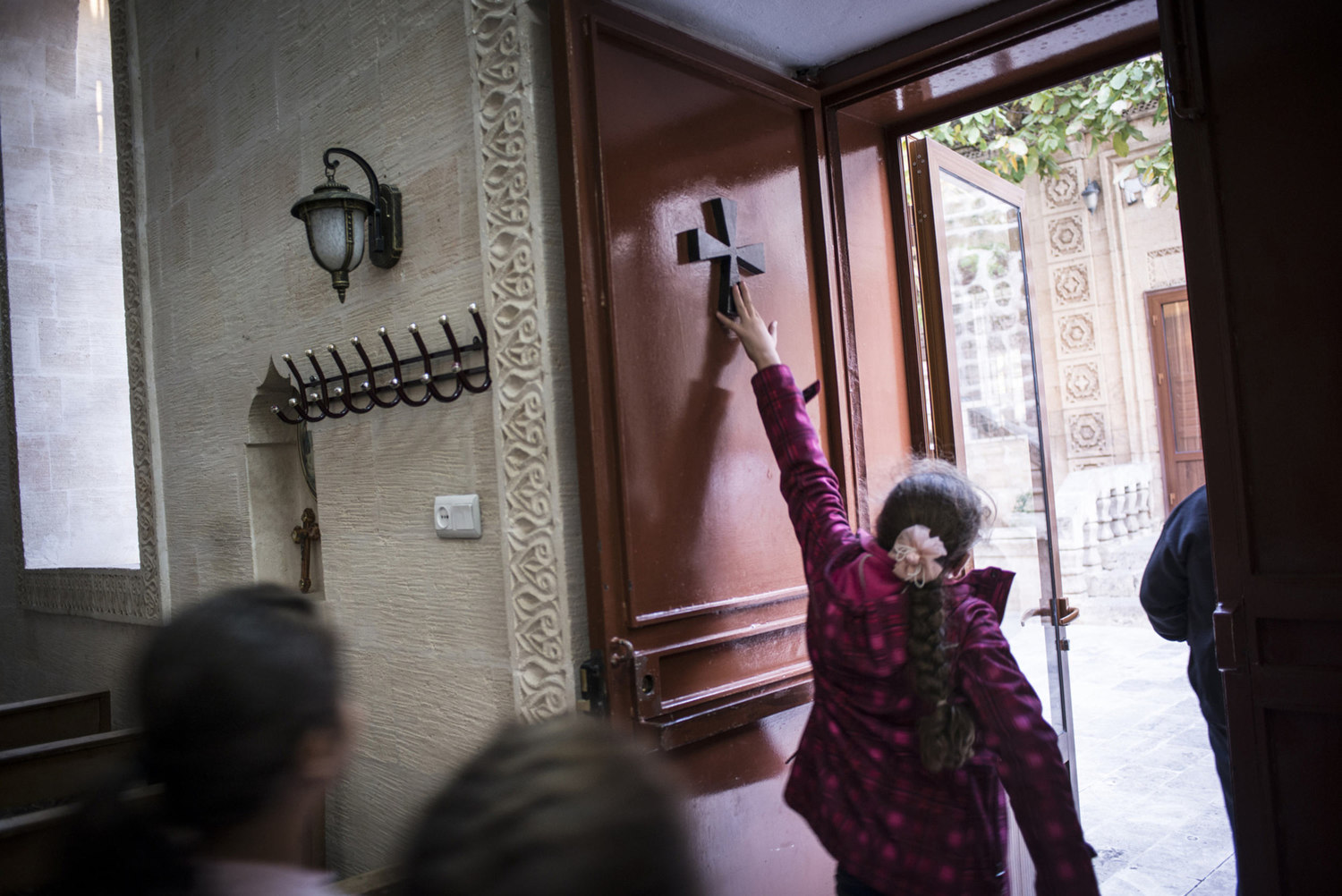 Members of the Asyrian community touch a cross on the door after praying at Mor Baraumo church during an afternoon service on October 30th, 2014.