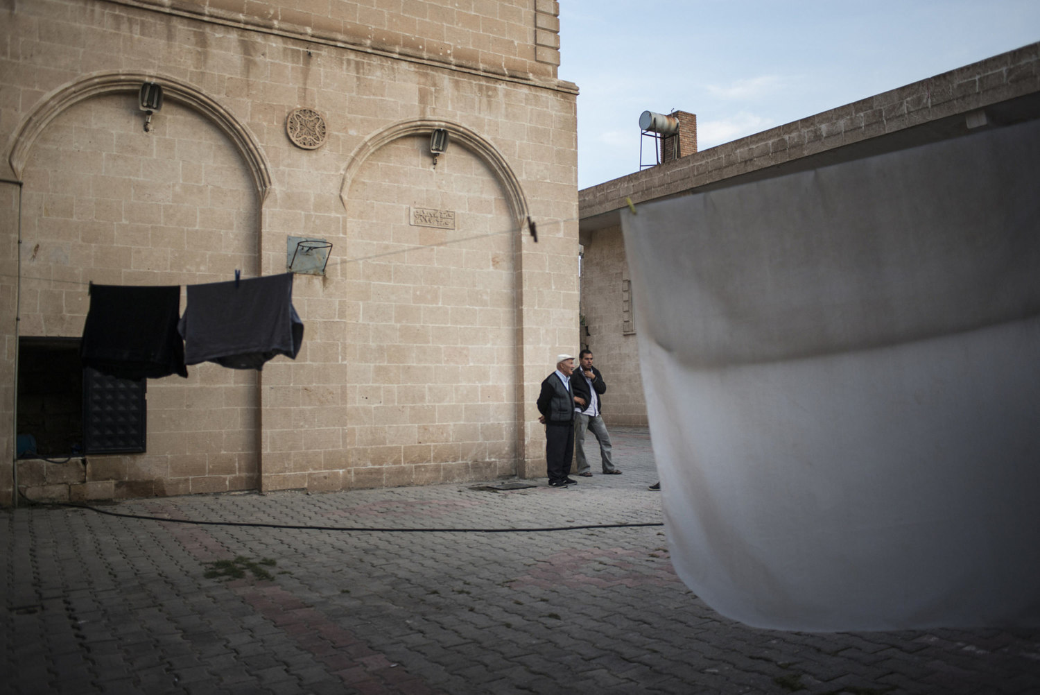 In the courtyard of the cultural center, Syrian refugees talk while laundry is drying on October 30th, 2014 in Midyat, Turkey.