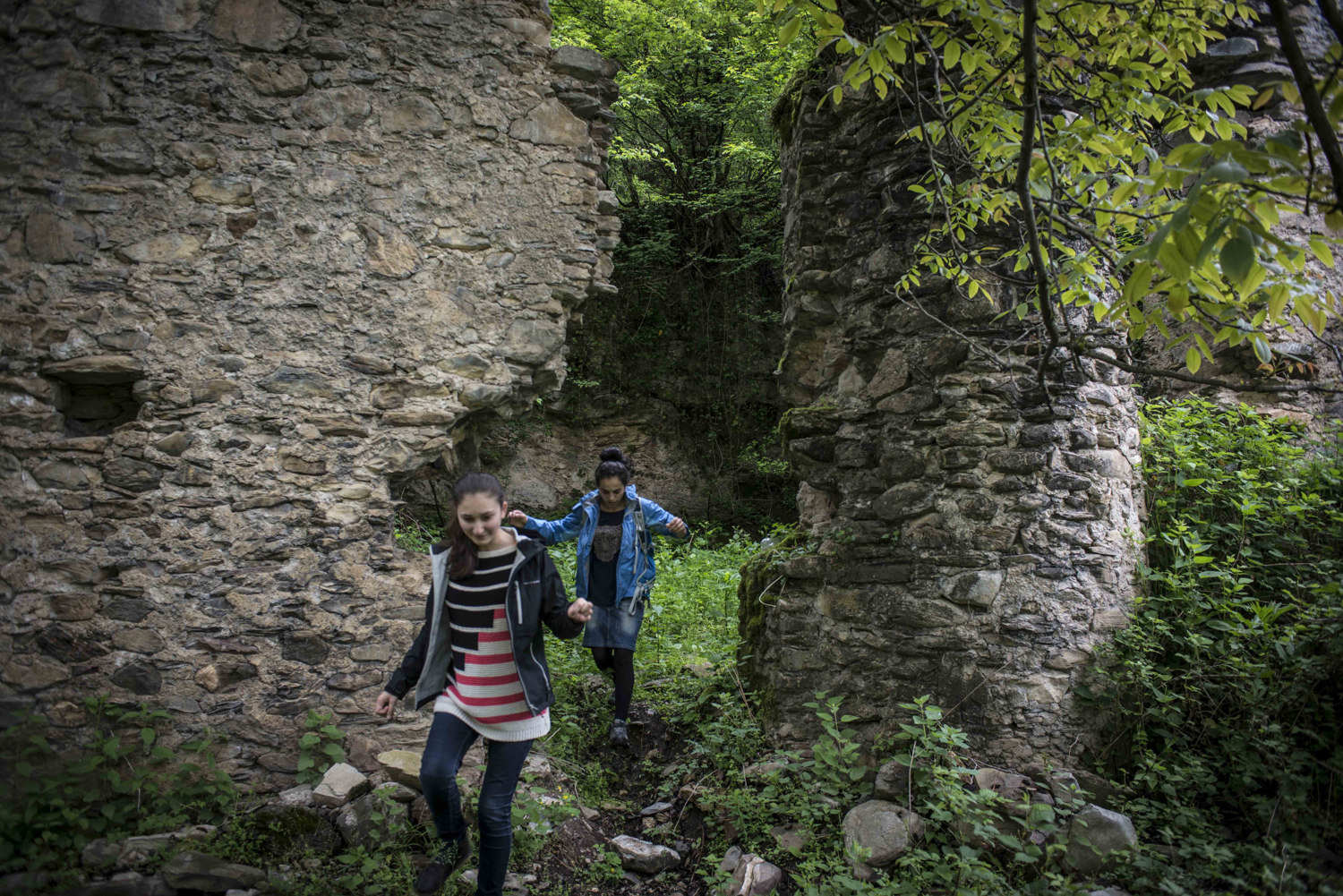 Two girls explore the remains of a Christian church.