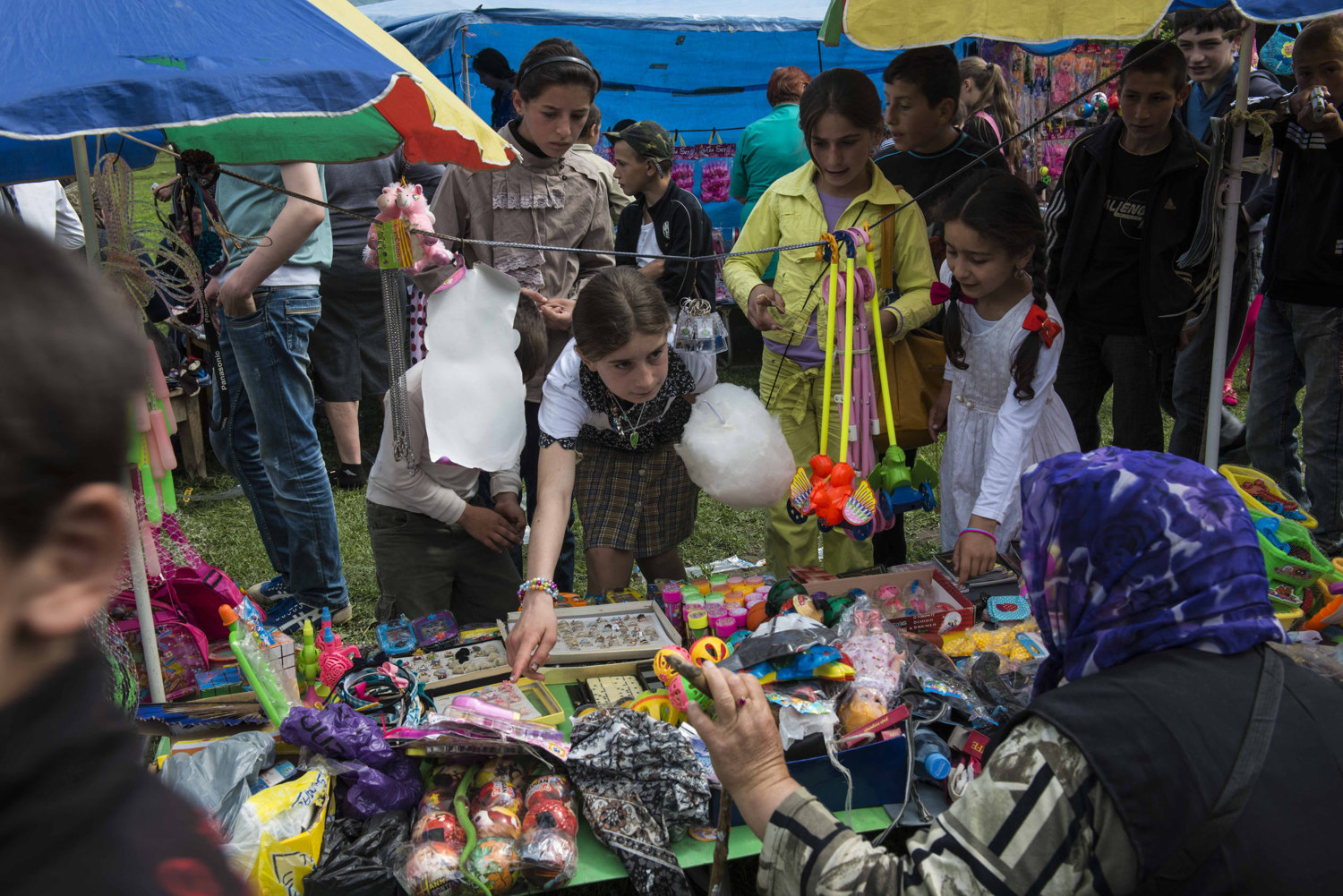 Girls buy trinkets and plastic jewelry at a fair held in honor of Victory Day in Duisi.