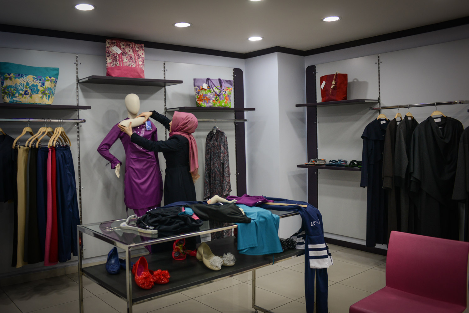 """A woman dresses a mannequin at the Hasema swimwear store in Fatih, Istanbul. Hasema is one of the main manufacturers of conservative bathing-suits and have a style similar to the """"Birkini""""."""