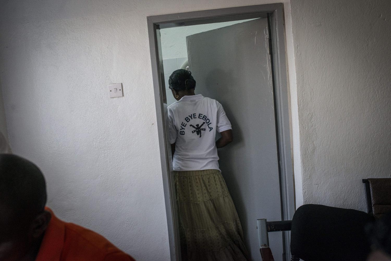"""An attendant wears a shirt saying """"Bye Bye Ebola""""."""