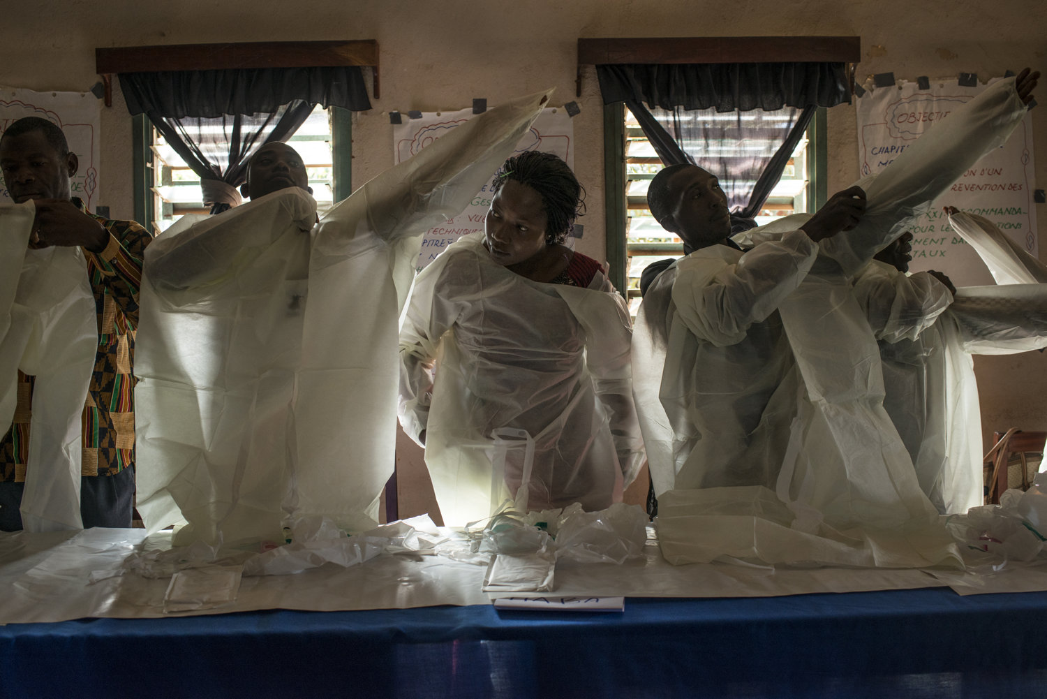 Elisa, center, practices putting on protective gear with her fellow students. Students are handed out protective gear to practice with on Day 2 of the JHIPAGO training. This session is led by Mrs Saran Kaba-in Faranah, Guinea on November 17th, 2015.