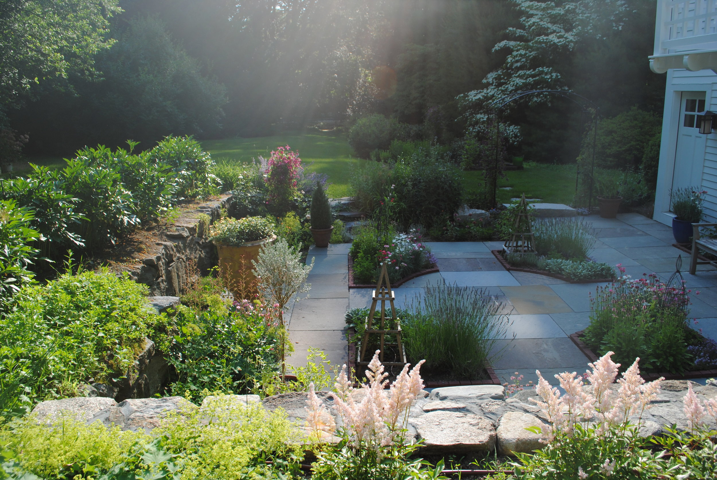 A dilapidated corrugated iron garage at side of garden is rebuilt and a formal herb garden with bluestone paving and beds is created in the sunken area.