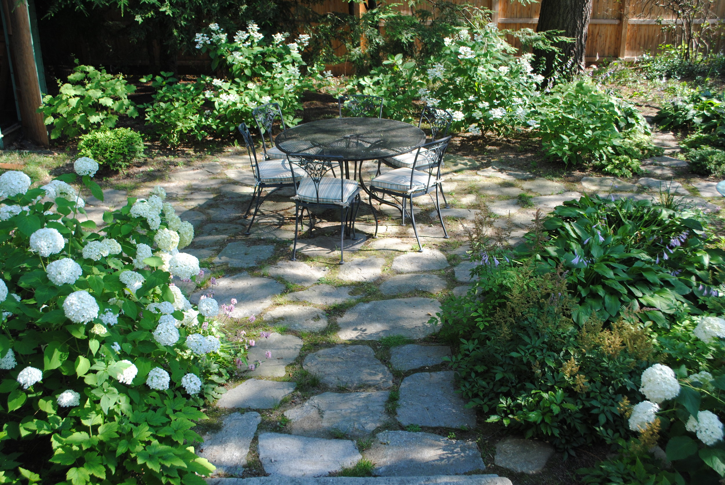 Awkward paths are reshaped to create a circular fieldstone patio, and shrubs and perennials replace the grass that is struggling in deep shade.
