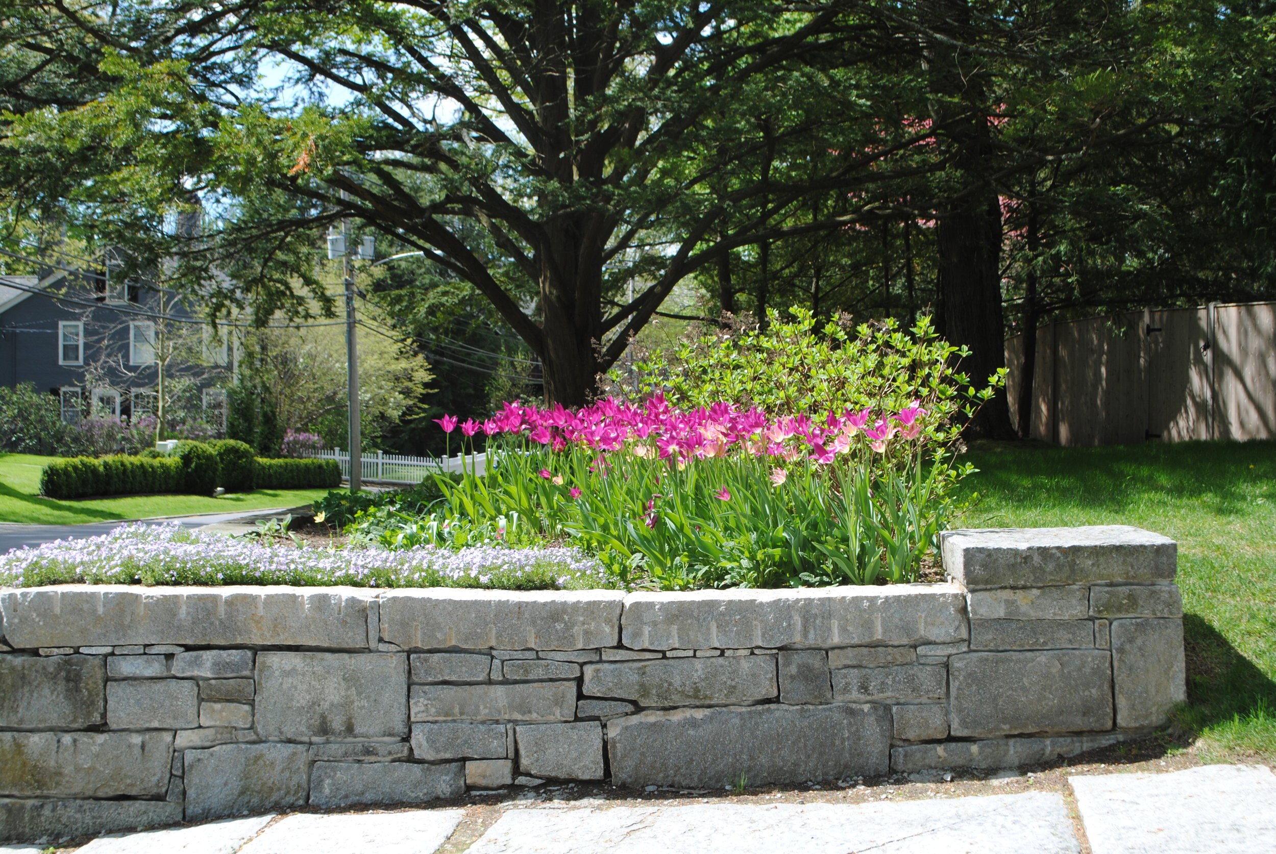 The granite is repurposed to repair the original old stone wall. The longer wall gives the bed more substance and impact.