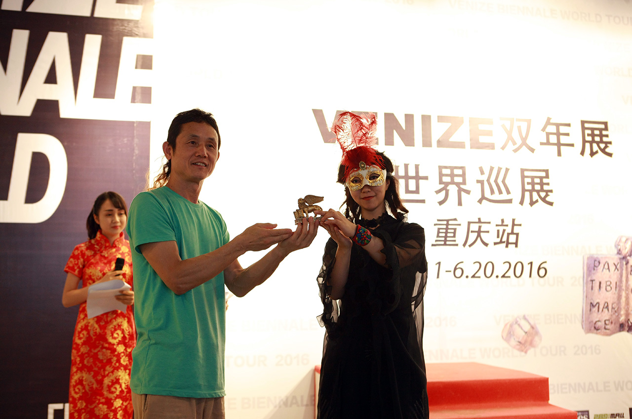"""After some welcome words by the hostesses, Tan Tan showed up with black long dress and typical Venetian mask. Curator Cai Qing went on the stage, awarded Tan Tan again with the famous """"Super Lion"""" that TanBo won from last years """"Venize Biennale"""", the audience burst into thunderous applause."""
