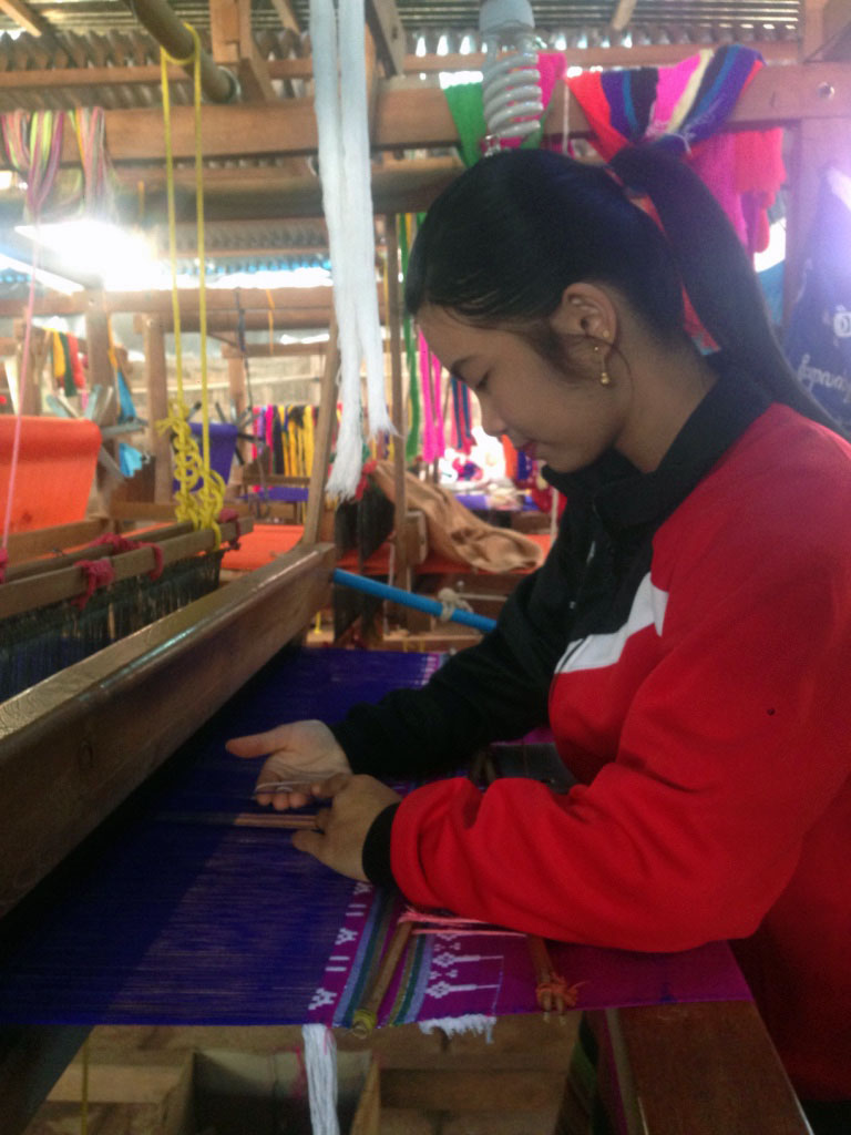 Nang Hom Khay on the Foot Pedal Loom. A Pedal Loom is an artisanal weaving method that uses the artisans feet to alternately lift and lower the thread.