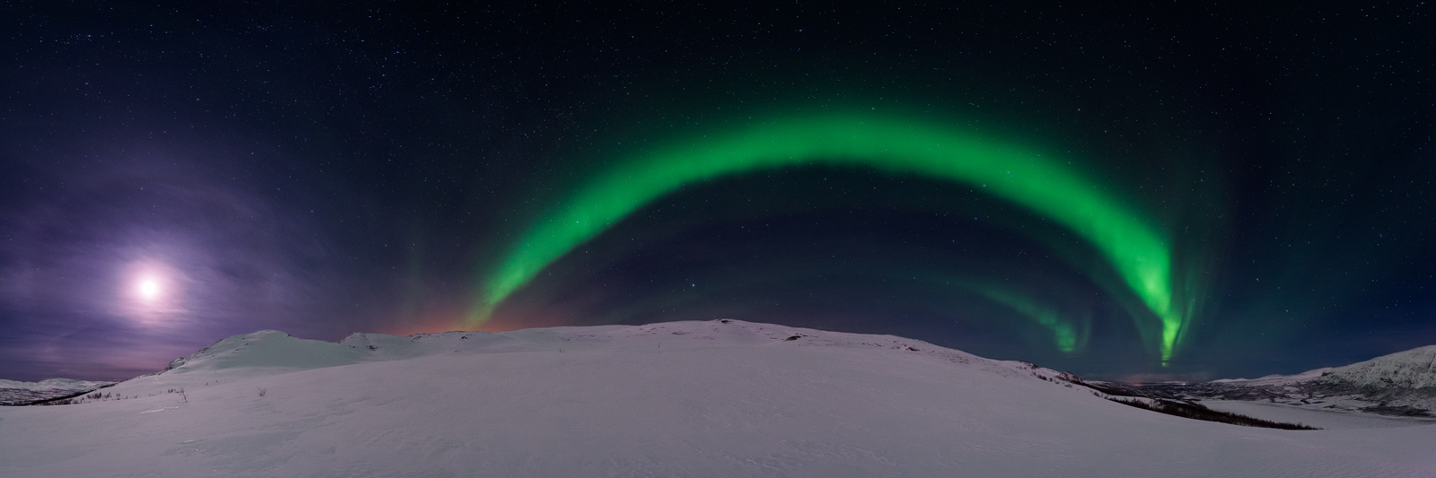 Panorama of an aurora arching the sky at Njunesgeahči mountain