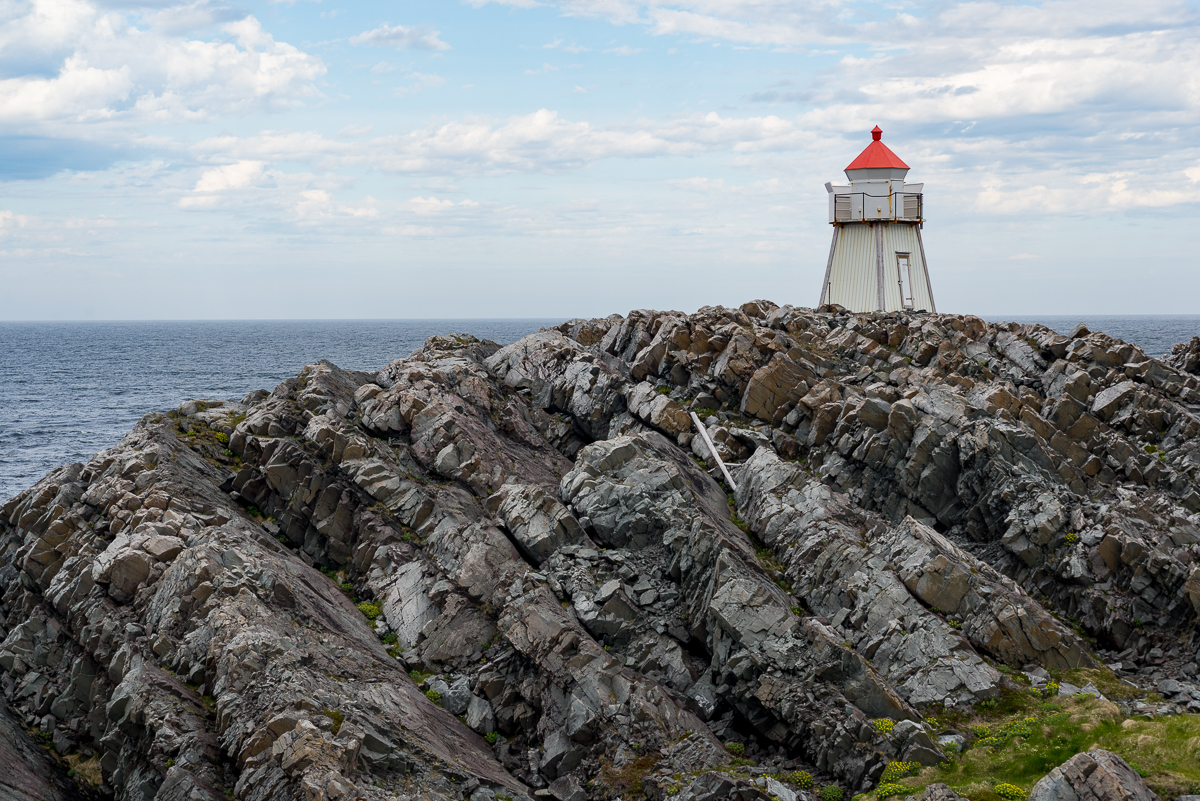 Lighthouse on the rocky shore of Hamningberg.