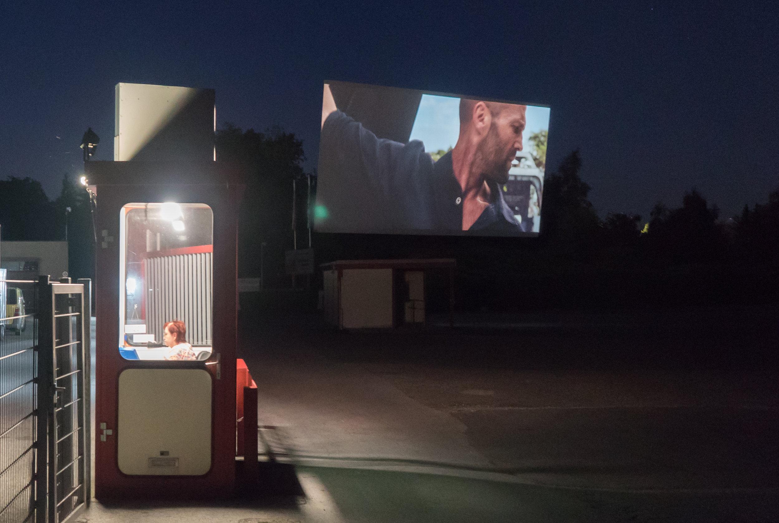 Im Drive In Autokino Essen: Kassenhäuschen und Leinwand mit Actionfilm