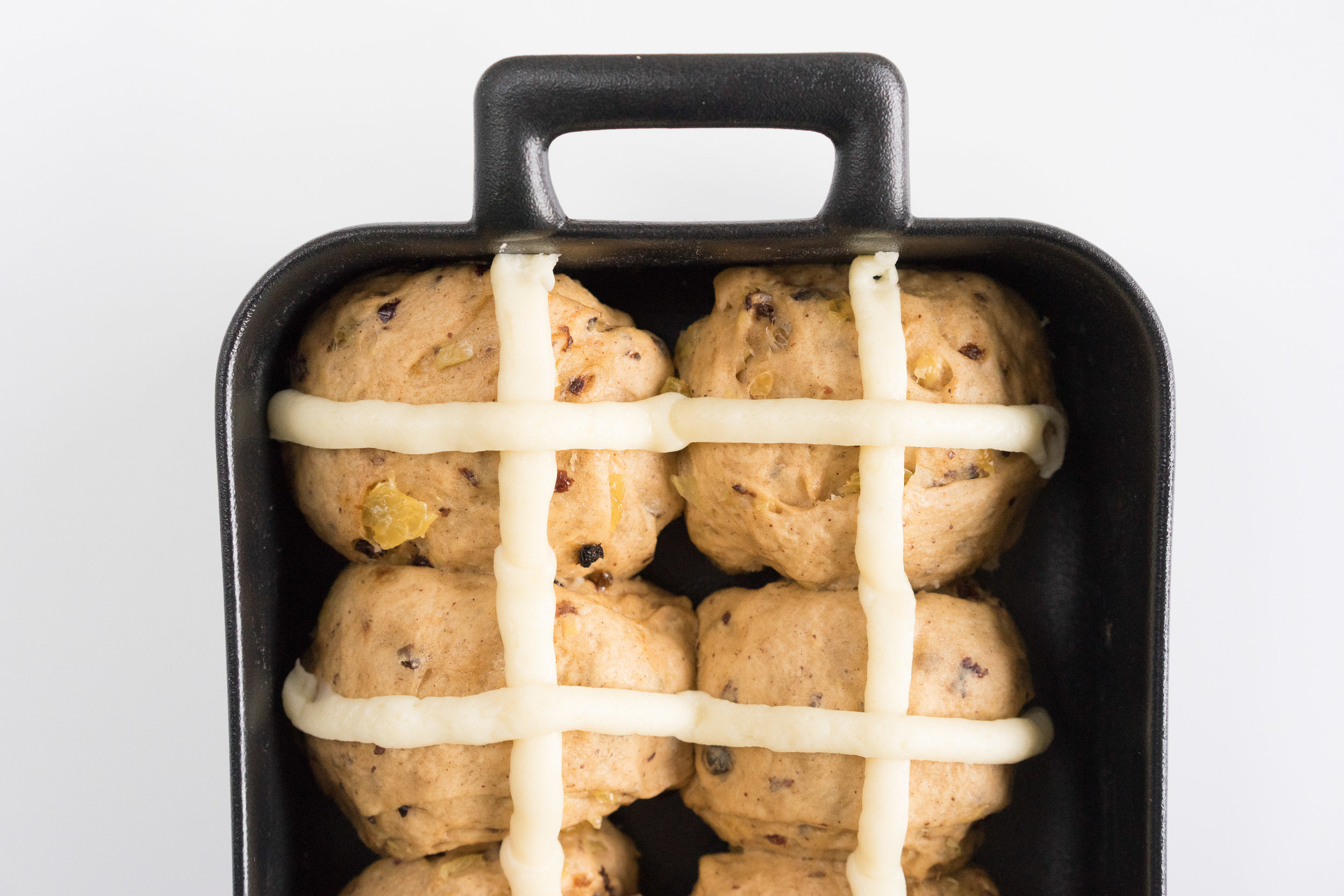 Vanilla Bean Glazed Hot Cross buns - fruity and spicy, with a choux pastry cross. Glazed with a vanilla bean glaze for a sweet, flavoursome finish. Perfect Easter baking treat.