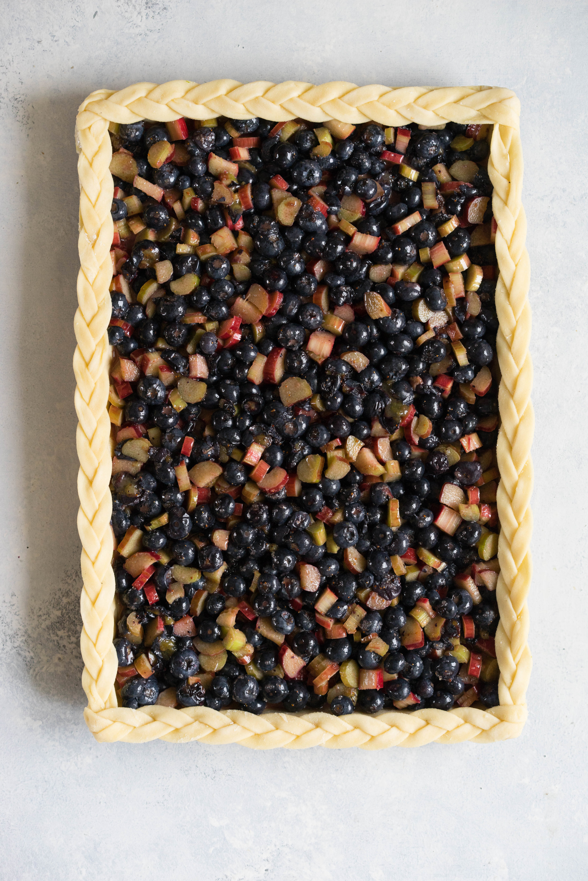 Blueberry and Rhubarb Slab pie - the ideal summer dessert for feeding a crowd! Flaky homemade pie crust is filled with a blueberry rhubarb filling before being topped with fun pie dough decorations then baked to perfection. #blueberry #rhubarb #slabpie #familypie #blueberryrhubarb