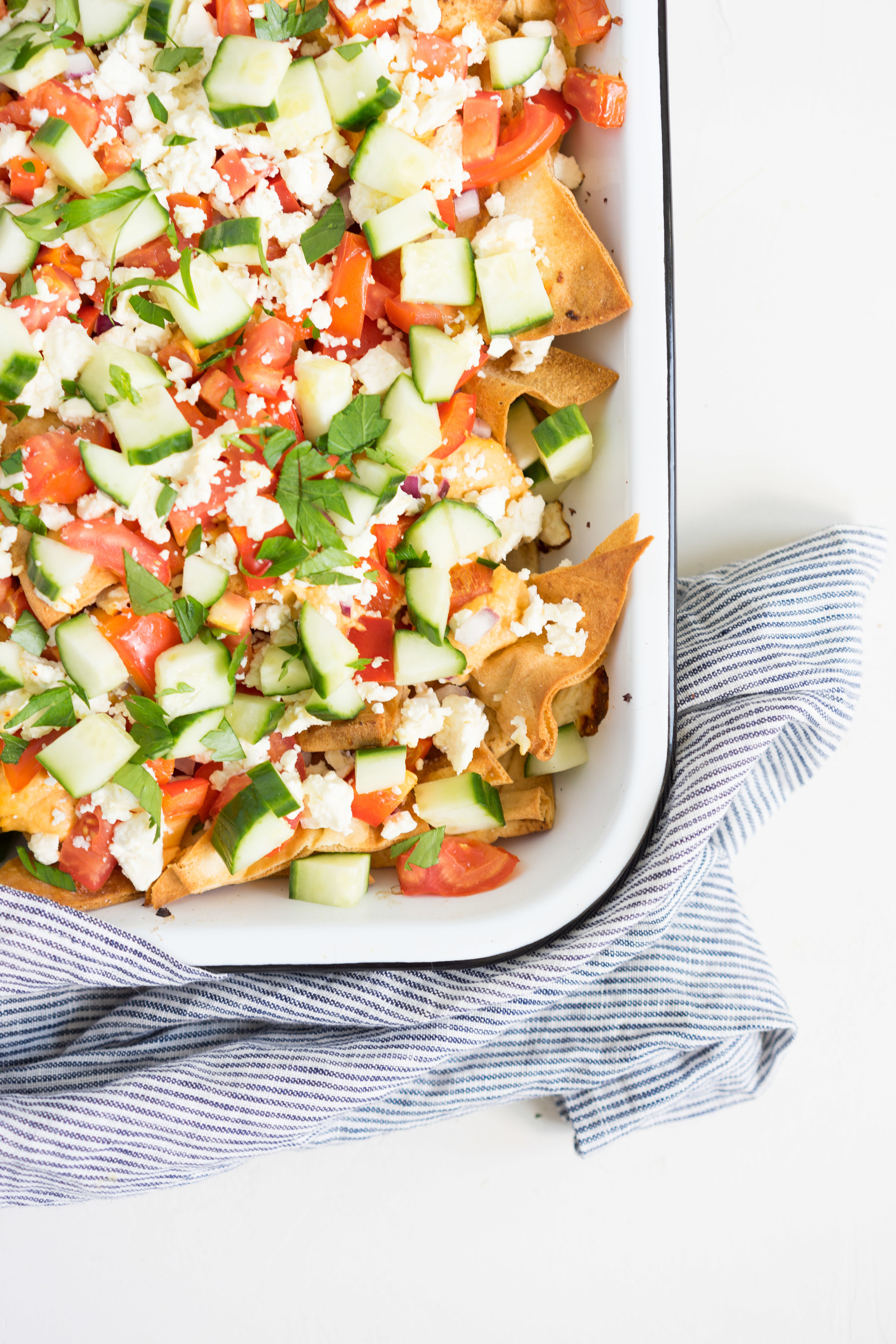 Greek Style Pita Bread Nachos - Homemade pita bread chips are layered with roasted red pepper hummus, feta cheese, red peppers, tomatoes and cucumbers, and loaded up with parsley. A delicious take on the classic nacho meal. #pitabread #greeknachos #hummusnachos #saladnachos #vegetarian