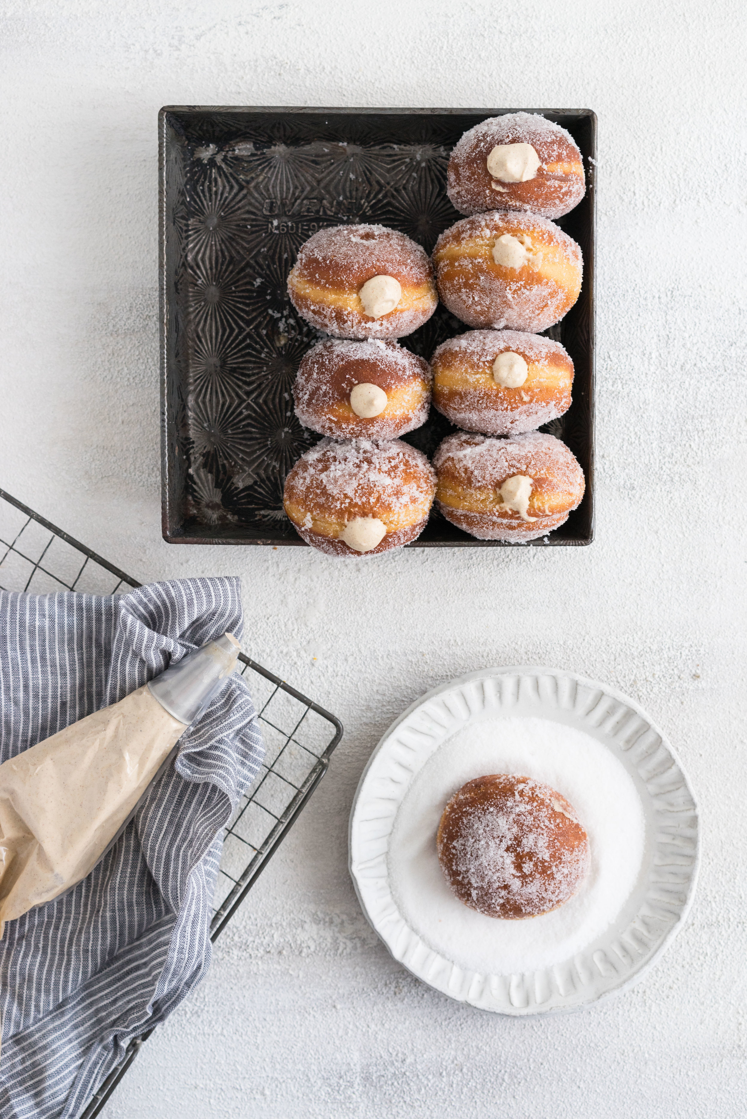 Gingerbread doughnuts with a spiced brown sugar diplomat cream. Pillowy brioche dough, spiced lightly with ginger and molasses, are stuffed with a light and creamy filling which is loaded with christmas spice. A perfect little package of holiday cheer