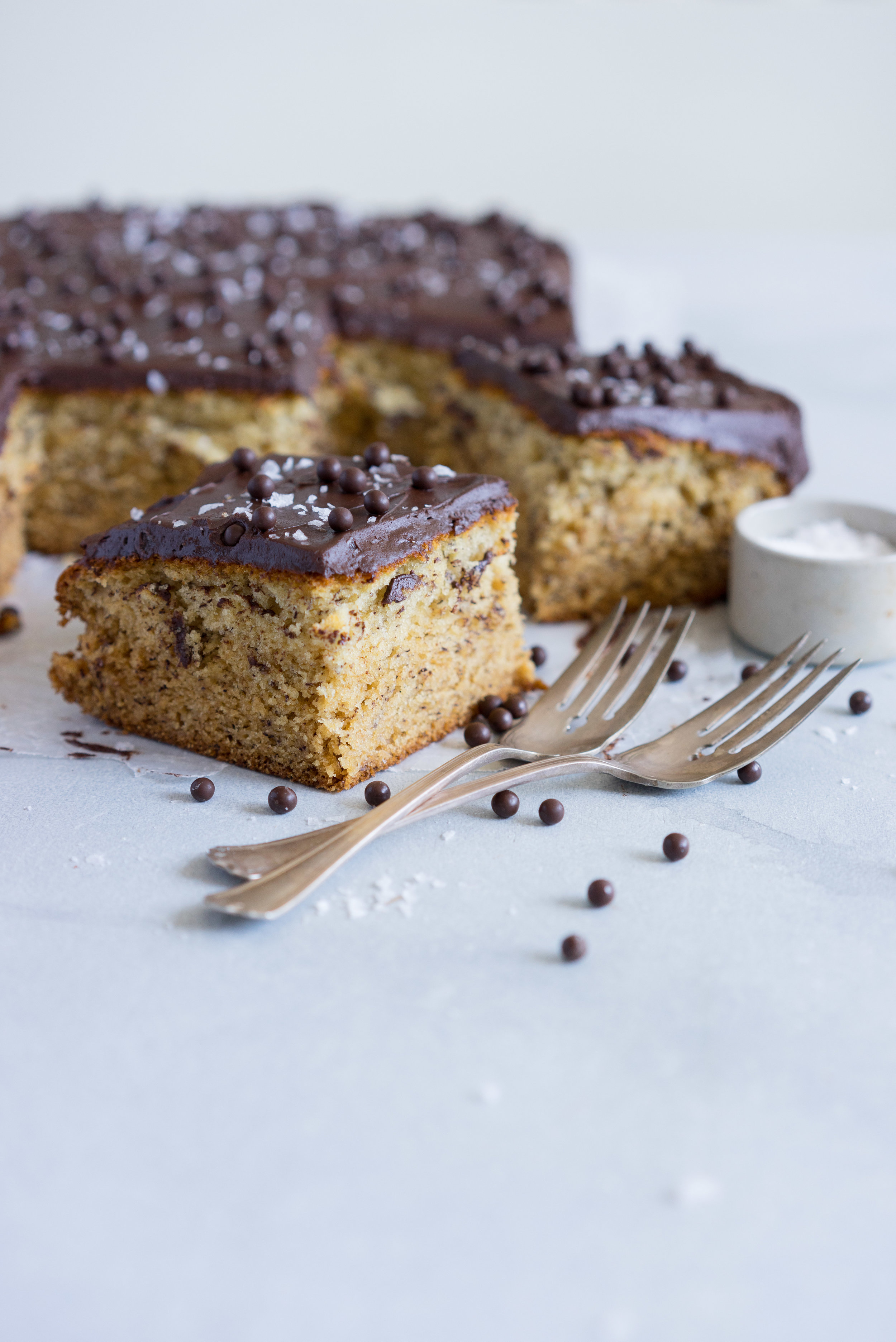 Banana Sheet Cake with Whipped Dark Chocolate Ganache. A little bit fancy but perfect for a crowd, this banana sheet cake will be your secret dessert weapon! #bananacake #sheetcake #chocolateganache #chocolatefrosting
