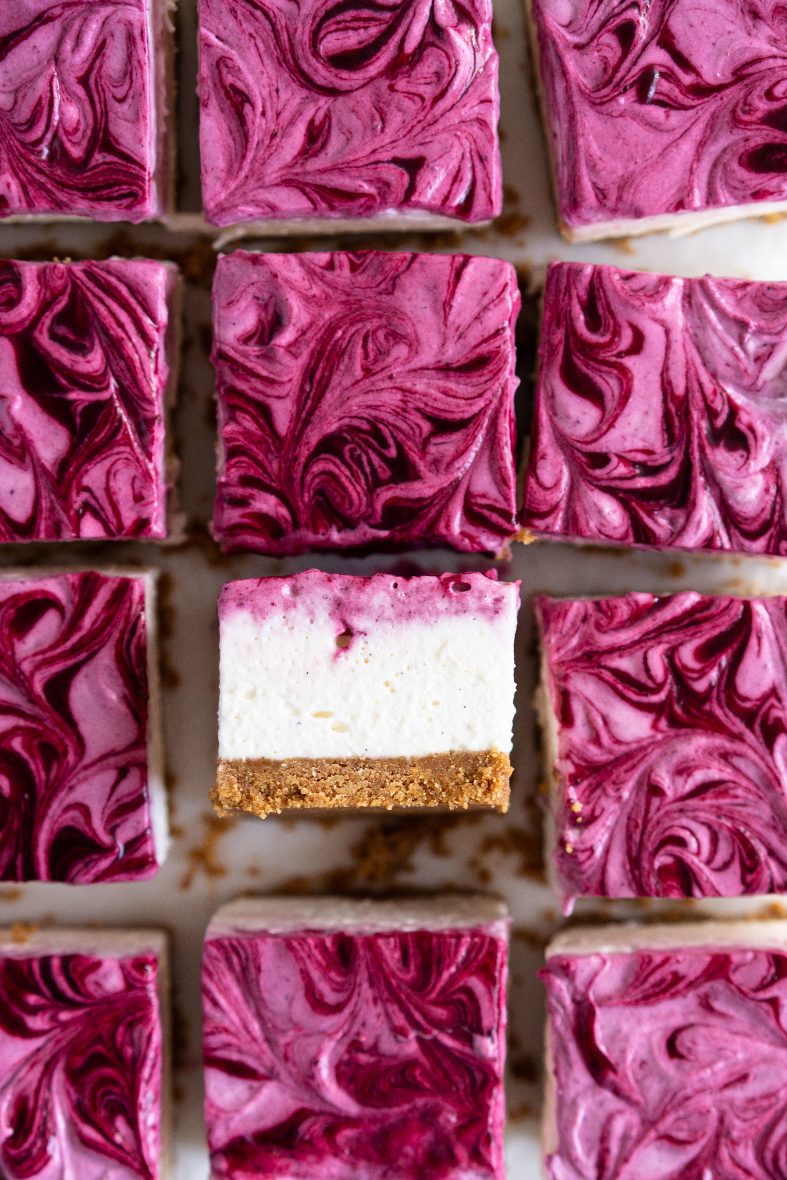 No Bake Mixed Berry Cheesecake Bars - delicious graham cracker crust, topped with a silky vanilla bean no bake filling, and finished with a beautiful marbled swirl of mixed berry coulis. perfect No bake, low effort dessert for any time of the year. #nobake #cheesecake #cheesecakebars #mixedberry #coulis