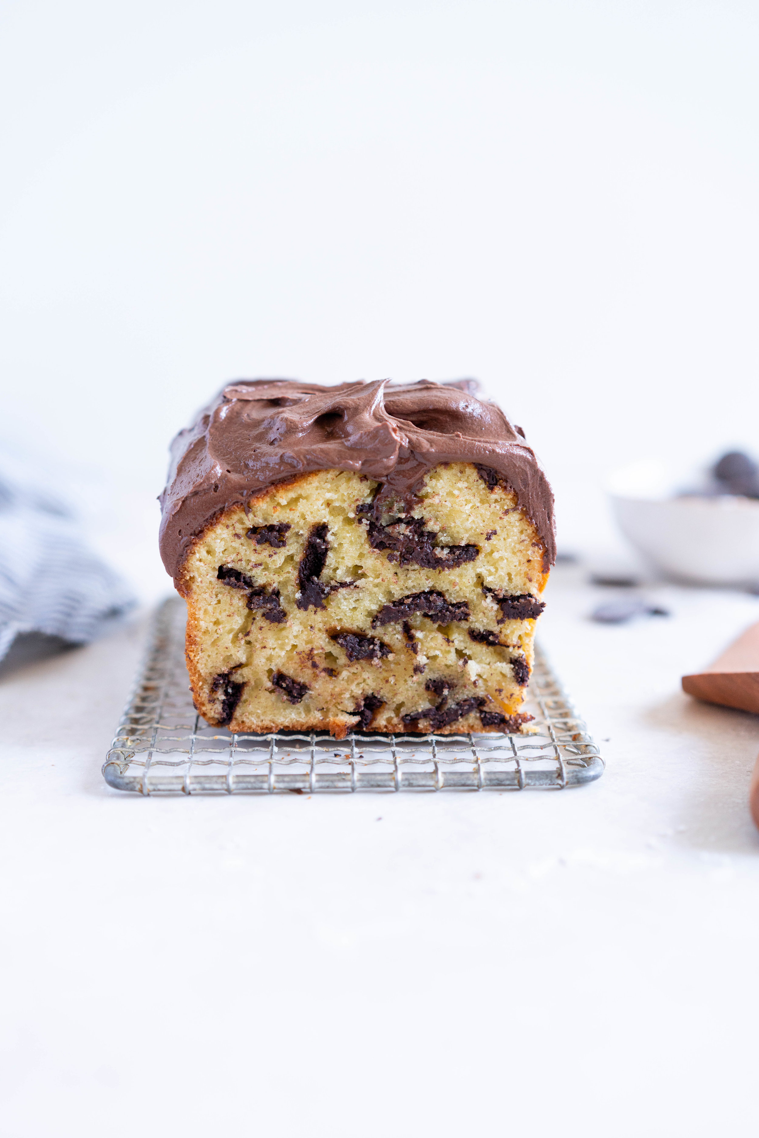 Chocolate Chunk Olive Oil Ricotta cake with Dark Chocolate buttercream - this cake is flavoursome from the olive oil, with a perfect crumb from the ricotta in the batter. It is studded with dark chocolate chunks throughout, and finished with a silky smooth dark chocolate buttercream. The perfect elevated loaf cake. #loafcake #poundcake #ricottacake