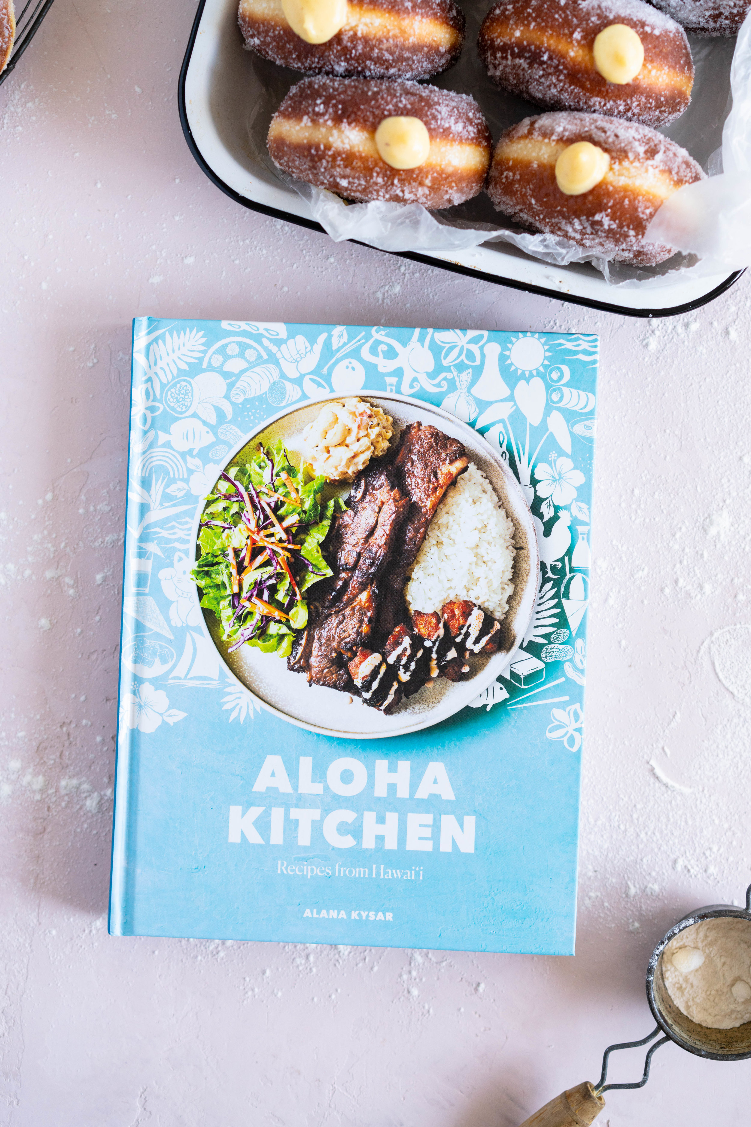 Malasadas with Liliko'i (Passionfruit) Pastry Cream Filling from Alana Kysar's new book, Aloha Kitchen. Malasadas are Portuguese style doughnuts, which are soft and fluffy. They are fried off, then rolled in sugar, then filled with a silky liliko'i pastry cream. These are the perfect indulgent treat, and are super easy to make. #malasadas #doughnuts #lilikoi #passionfruit