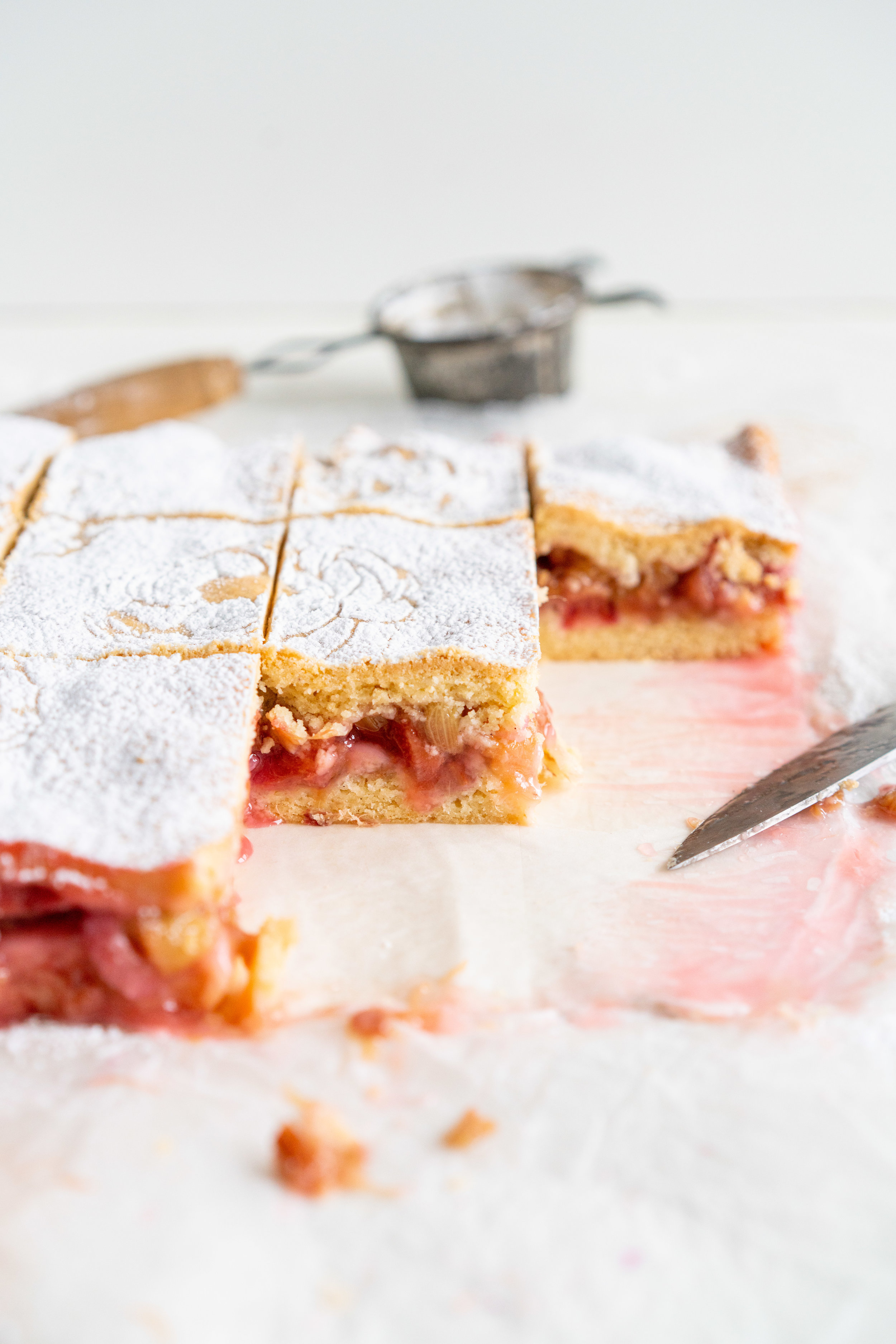 Rhubarb Shortcake Bars - Two layers of sweet, short pastry enclose a jammy, rhubarb centre. These rhubarb shortcake bars differ from traditional American shortcake in that they are all baked together, giving you a range in texture - crisp pastry, soft where it hits the tart rhubarb centre, and a dusting of powdered sugar to finish. This recipe is amazingly versatile and works great with any stone fruit or berries. #rhubarb #rhubarbshortcake #shortcake #newzealandshortcake shortcake bars.jpg