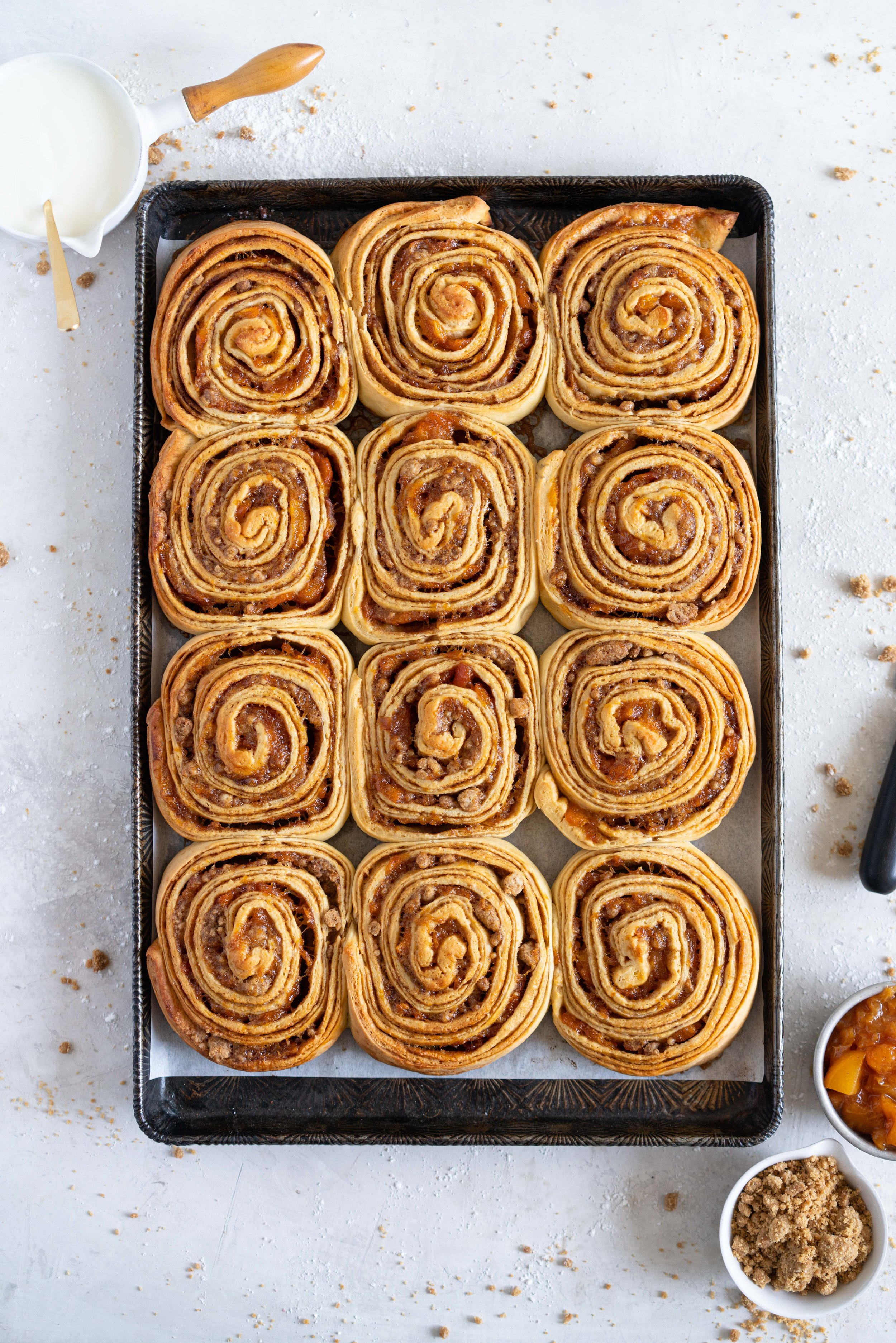 Laminated brioche cinnamon buns with peach compote and brown butter streusel. Soft and fluffy brioche is layered with cinnamon sugar, then filled with a brown butter streusel and peach compote, and finished with a powdered sugar glaze. These are the perfect summer treat. #briochebuns #cinnamonbuns #laminatedbriochebuns #peachcompote