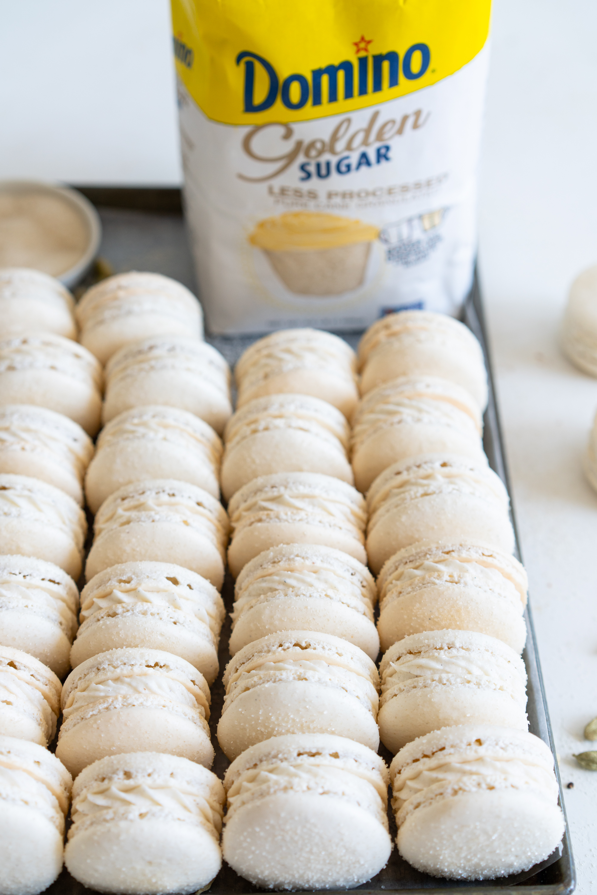 Golden Sugar Macarons with Cardamom Cream Cheese Filling. These French macarons are made with golden sugar, sprinkled with the sugar to give them a sparkly top, and filled with a smooth cardamom cream cheese filling. These are an easy gluten free treat, and this is a great go-to macaron recipe, filled with tips and tricks to help you master french macarons! #frenchmacarons #goldensugar #cardamomcreamcheese