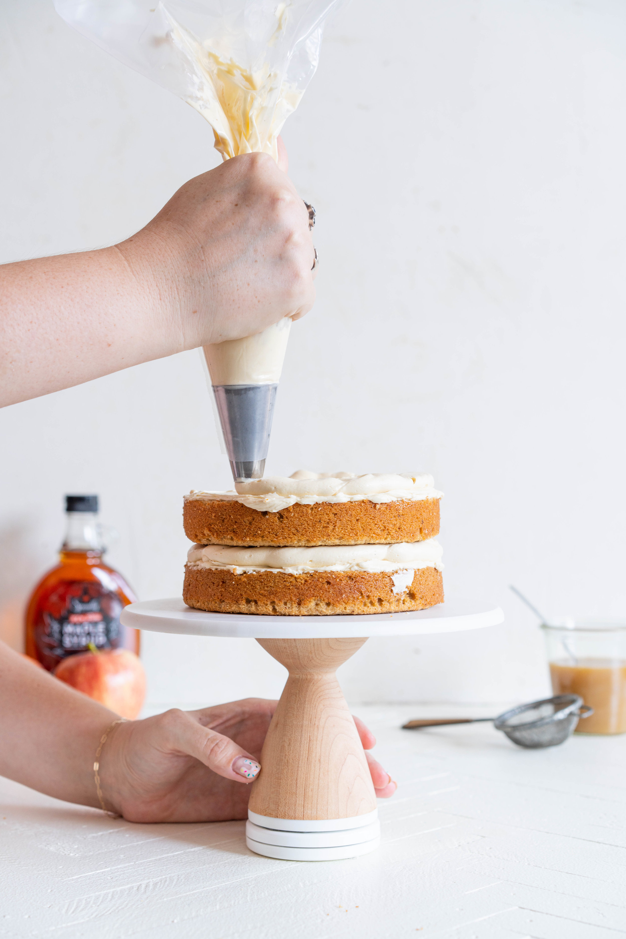 Spiced Brown Sugar cake with Cinnamon Apple Filling and Maple Caramel German Buttercream. This layer cake screams fall - a cozy brown sugar spice cake is layered with a cinnamon apple filling and a maple caramel german buttercream, then finished with a maple salted caramel drizzle and a dusting of cinnamon. This is the perfect fall inspired layer cake #autumncake #applecake #layercake
