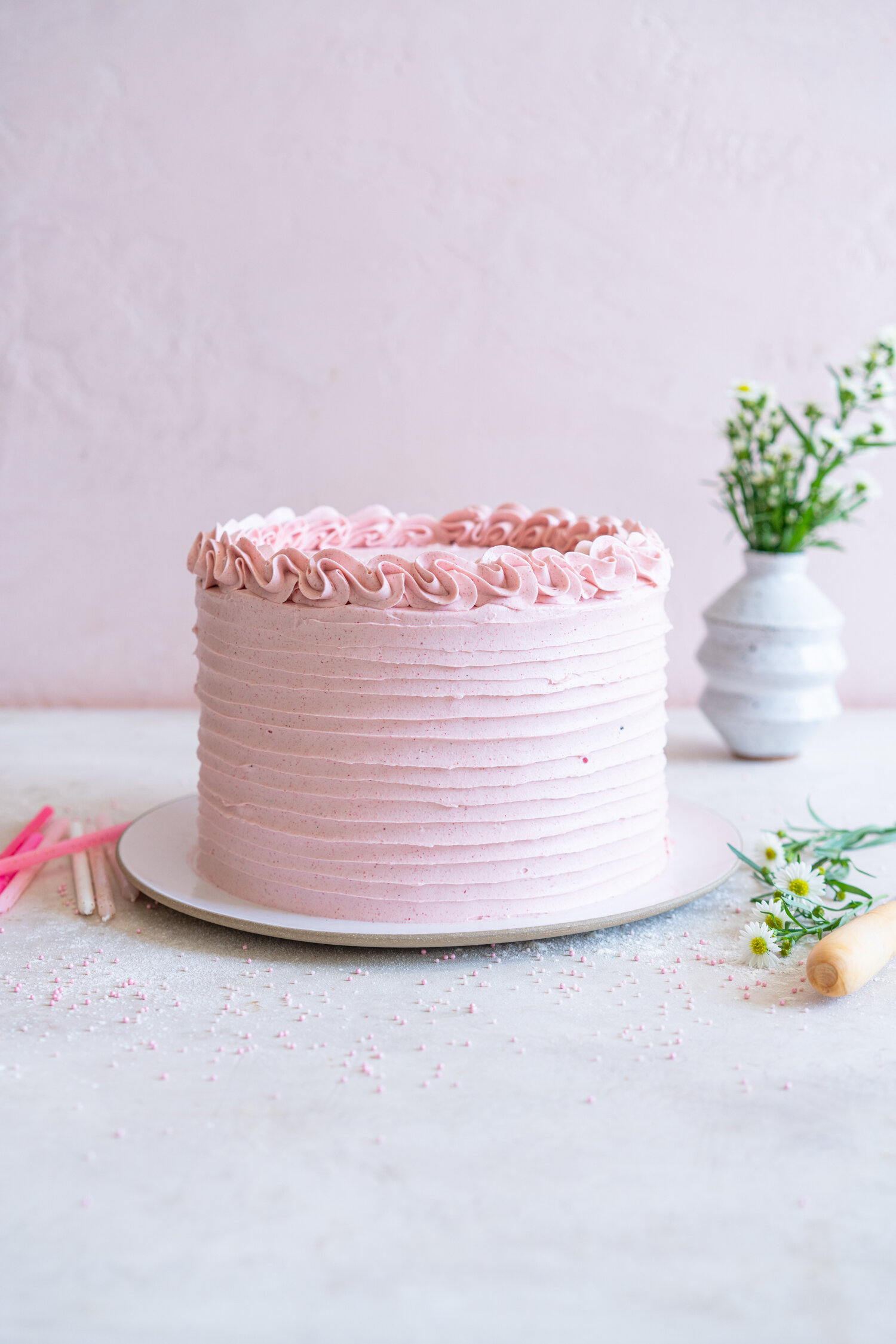 Chocolate Layer Cake with Jam Filling and Strawberry Swiss Meringue Buttercream from Amanda Faber's book, Cake Portfolio. Layers of Rich chocolate cake are layered up with mixed berry jam, and then the cake is finished with a strawberry swiss meringue buttercream made with freeze dried strawberry powder. This is the perfect birthday or celebration cake for anyone who loves strawberry or chocolate. #strawberryswissmeringuebuttercream #chocolatelayercake #layercake