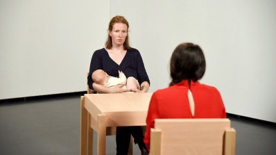"Hannah Cooke, Ada vs Abramović (2018). The slow motion video shows Hannah Cooke breastfeeding her daughter Ada in an exhibition like setting. They are sitting in front of a woman in a red dress that looks like Marina Abramović in her performance ""The Artist is Present"", which was shown at MoMA 2010."