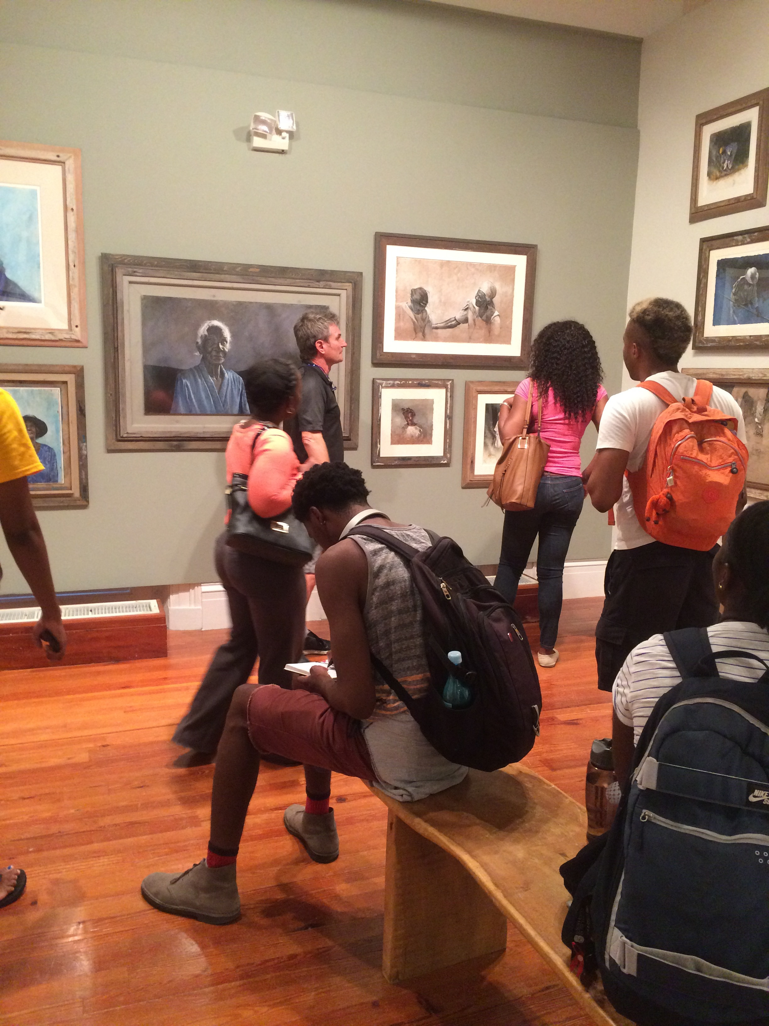"""University of The Bahamas students visit Thierry Lamare's """"Love, Loss and Life"""" on view at the National Art Gallery of The Bahamas and receive a guided tour by the artist. Students ask questions and take notes of the images on view."""