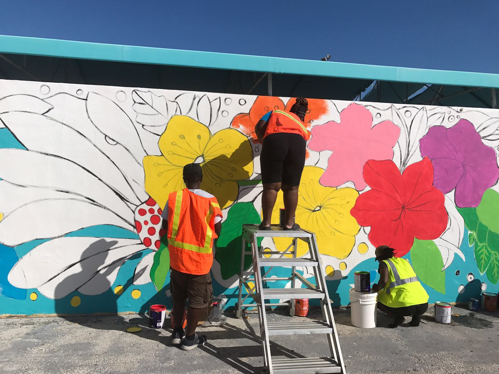 NAGB staff and Exuma community artists work on the airport mural, supported by the Ministry of Tourism.