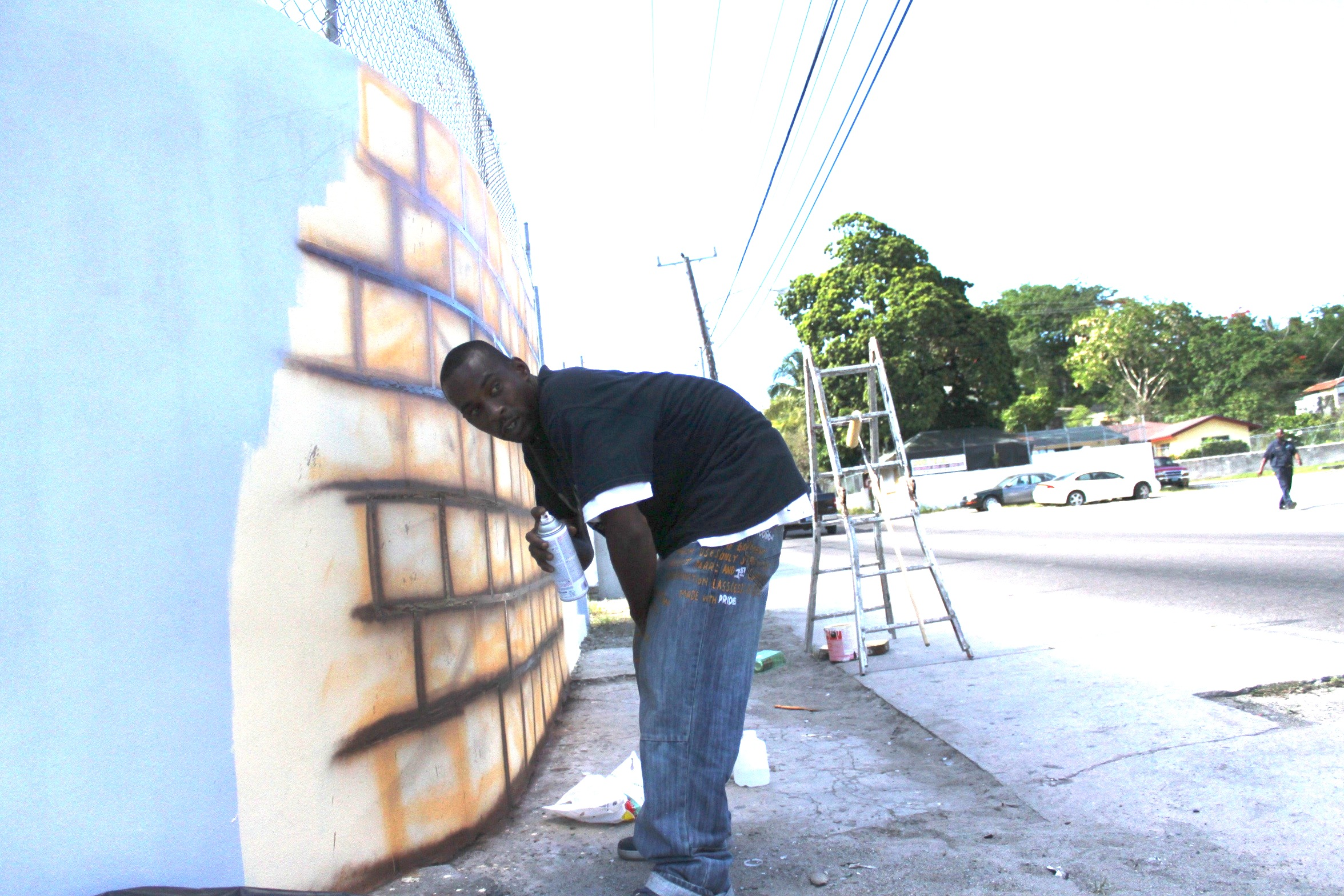 """Slime working on the """"Wall of Respect,"""" East Street and Lewis Street, 2015. All images provided by Amanda Coulson."""