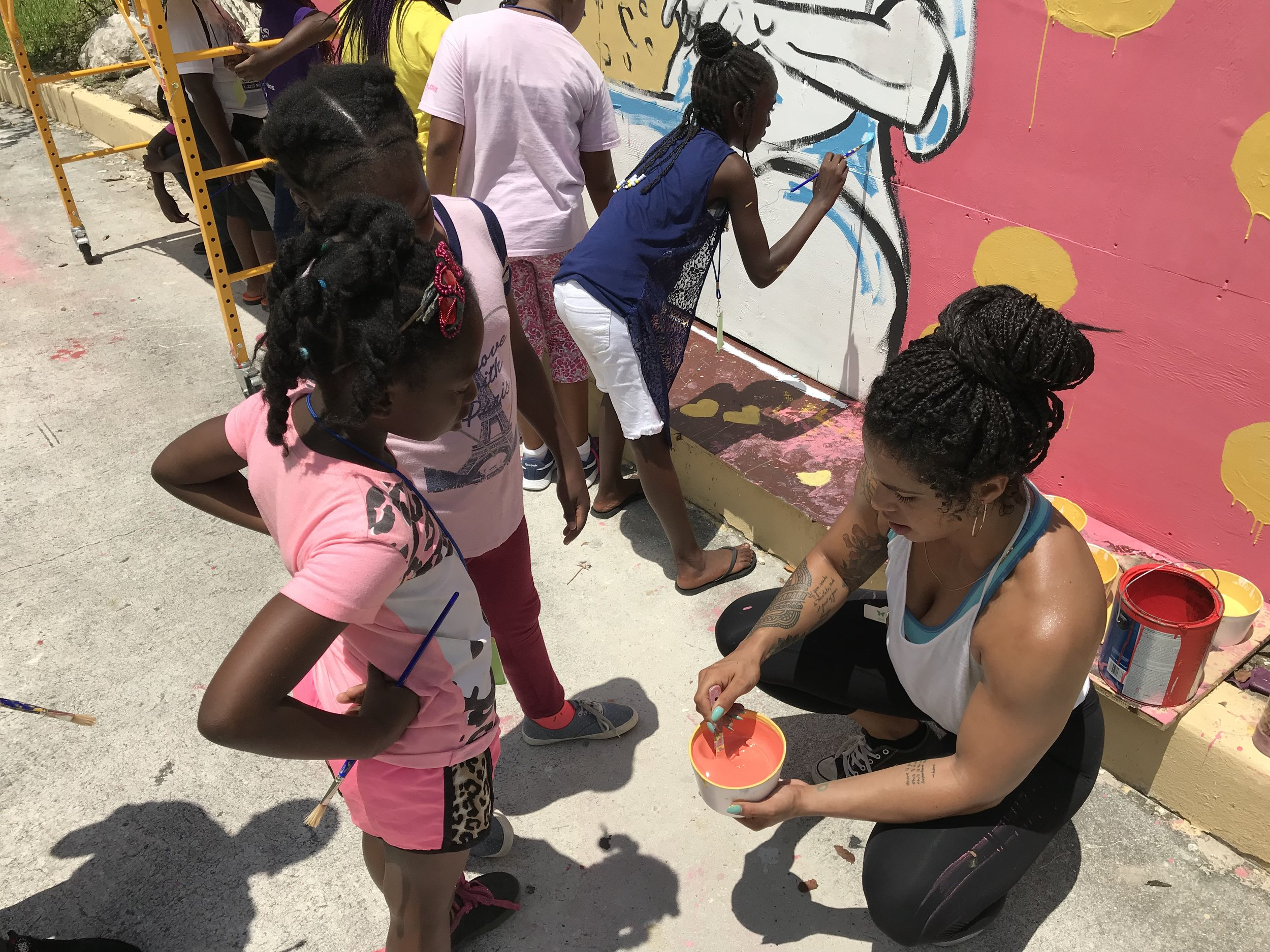 Mural artist, Angelika Wallace-Whitfield, gives a quick paint mixing lesson.
