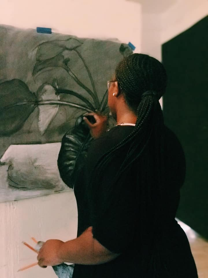 Minnis at work on a charcoal drawing of a plant. Image courtesy of the artist.
