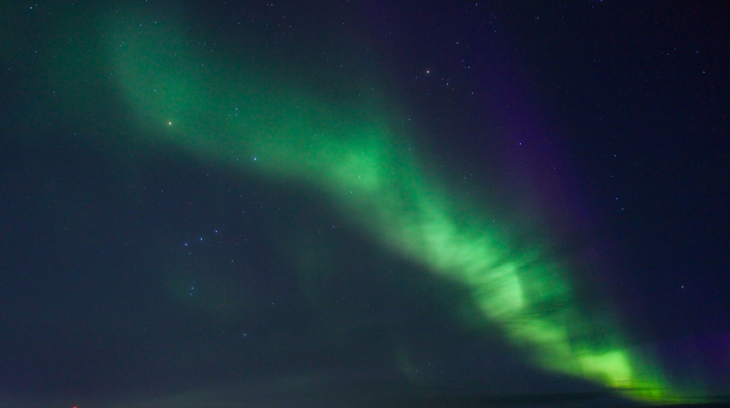 Green and purple aurora, around 9:30 PM in Ilulissat, Greenland (Photo by Andrew Evans)