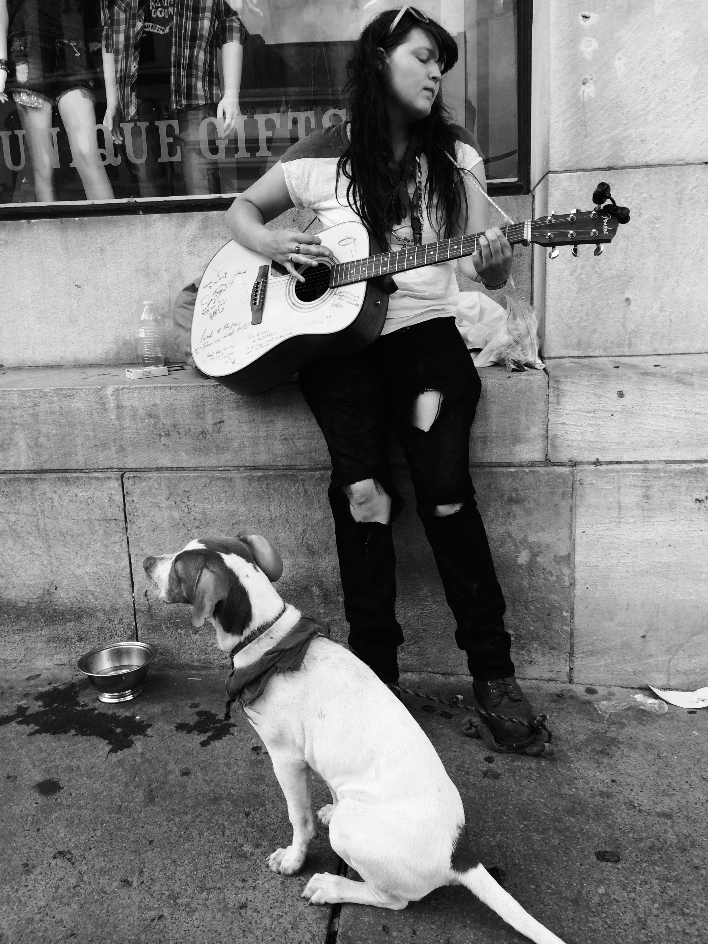 An aspiring country music star busks on Broadway, while her dog listens patiently in the heart of Nashville's honky tonk district. (Photo by Andrew Evans)